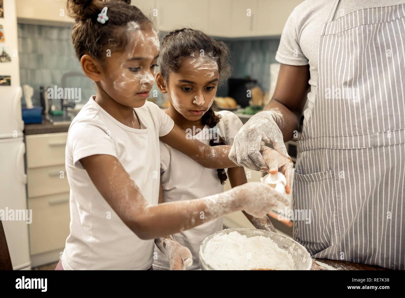 Dos chicas divertidas con bonitos peinados de cocinar juntos en el fin de semana Foto de stock