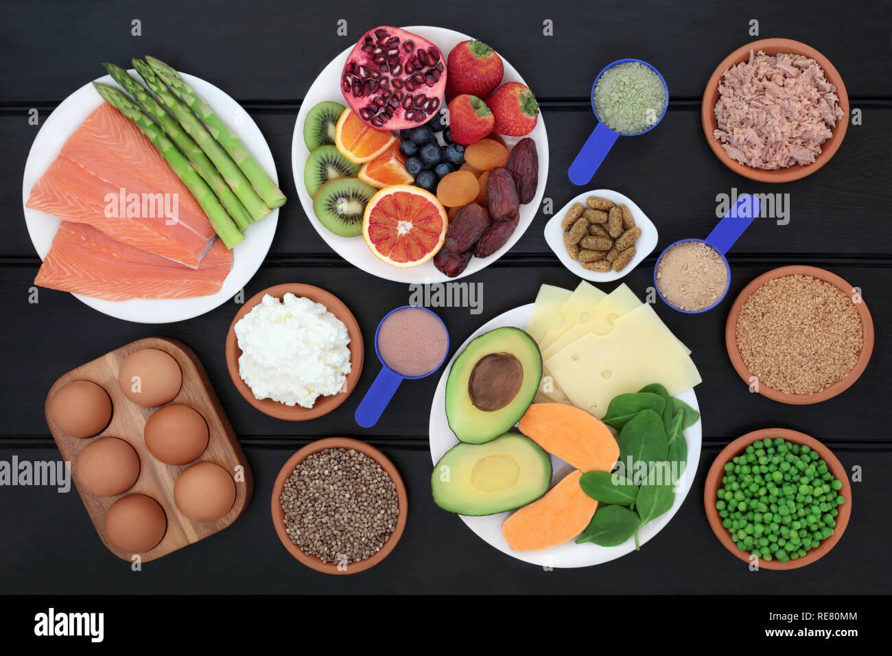 Alimentos saludables para los constructores del cuerpo con alto contenido  en proteínas, incluidos los peces, productos lácteos, suplemento dietético  de polvos y multi pastillas de vitaminas, frutas, vegetales y semillas  Fotografía de