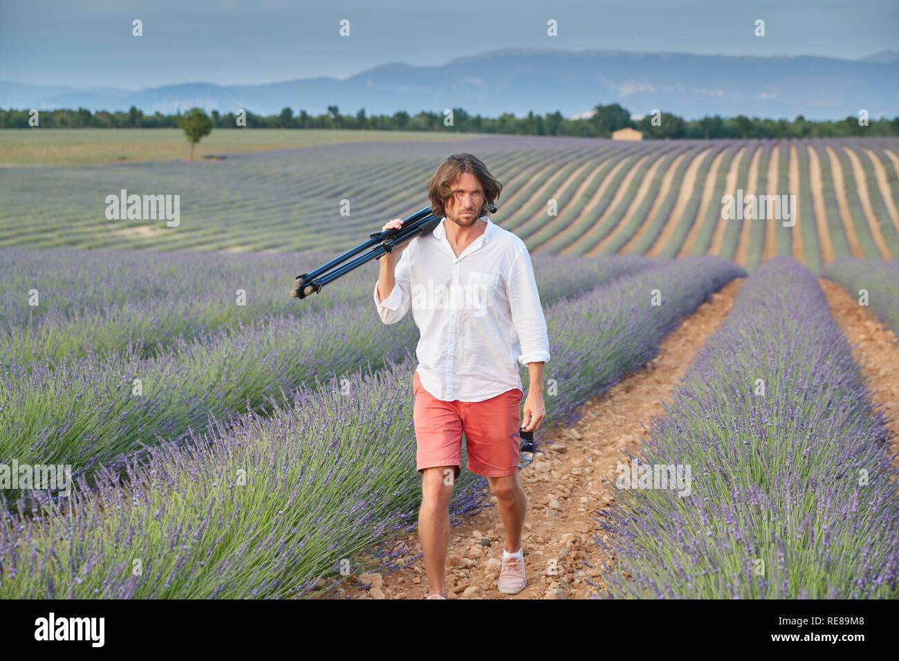 La hermosa joven hombre brutal va a un campo lila al atardecer, él está vestido con una camisa blanca de manga corta y calzones rojos, el fotógrafo Imagen De Stock