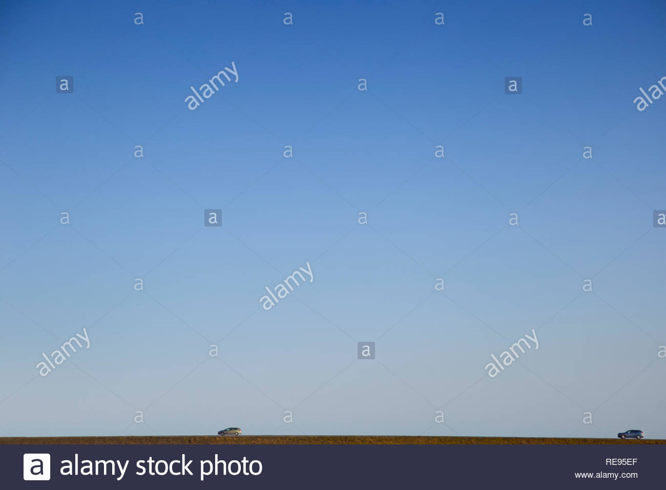 Una imagen minimalista de Islandia en el que dos coches son vistos a lo lejos bajo un cielo azul sin nubes grande Imagen De Stock