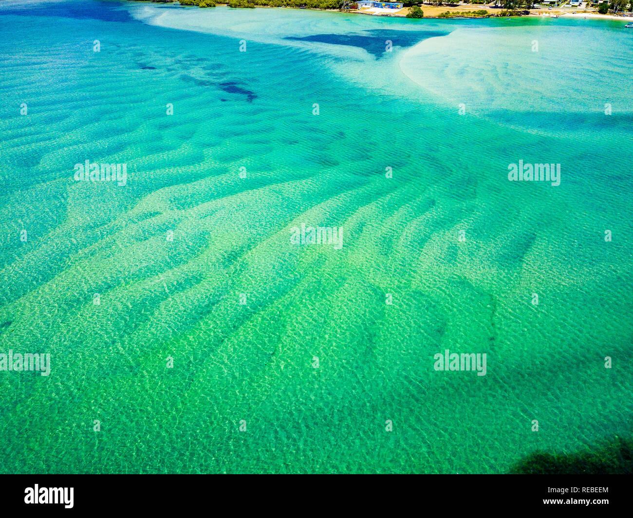 Patrones y texturas increíbles dejada por la arena con agua de color turquesa brillante arriba. Pumicestone Passage, la Sunshine Coast, Queensland, Australia. Foto de stock