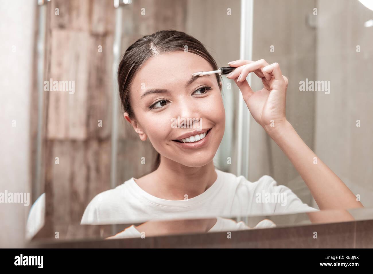 Morena empresaria usando mascara de gel para cejas Imagen De Stock