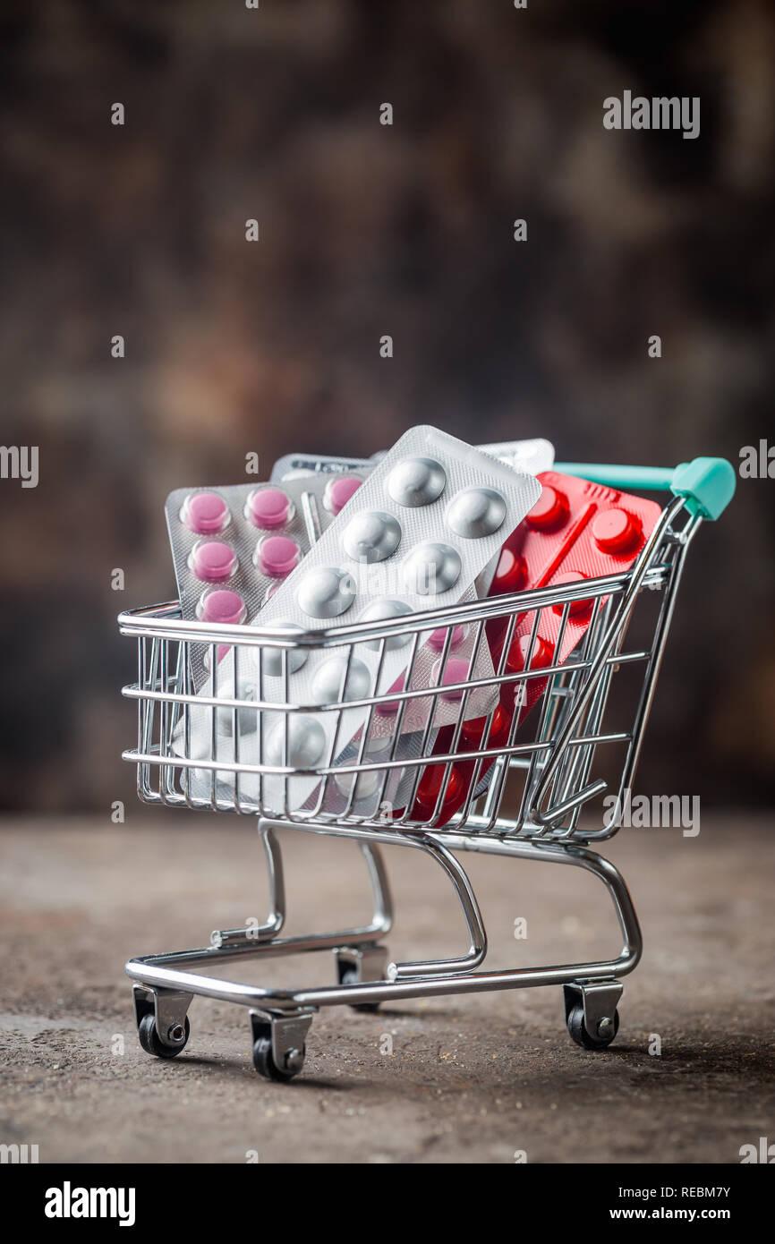 Compras llena con píldoras sobre fondo oscuro. Concepto: conjunto completo de medicamentos en el almacén. Espacio para el texto copia Foto de stock