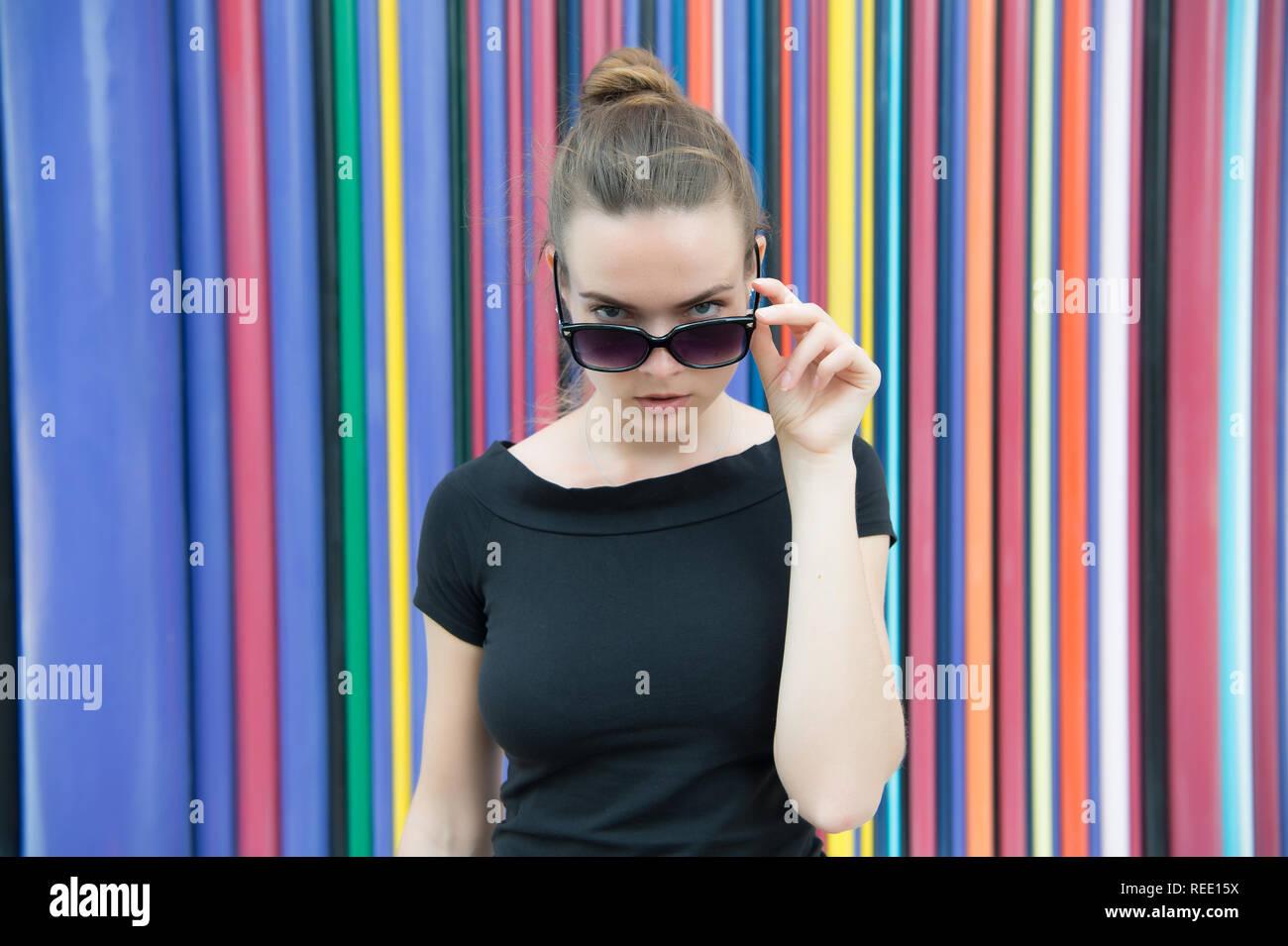 Concepto de estilo urbano de moda. Señora misterioso rostro sacando de anteojos negros en frente de la pared multicolor rayas en París. Mujer elegante apariencia elegante traje. Moda urbana de las grandes ciudades. Imagen De Stock