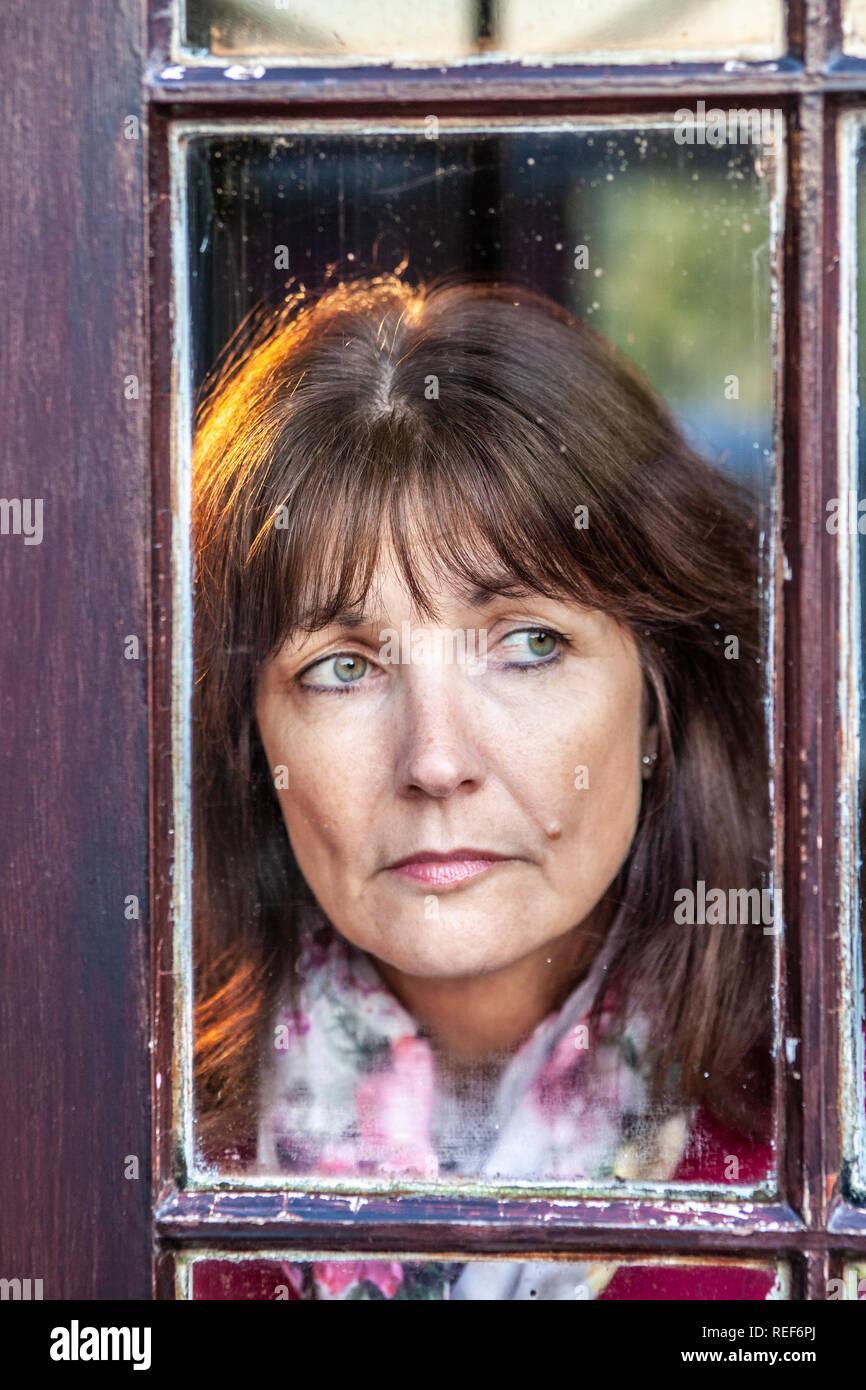 Publicado modelo atractiva, soltera, mirando por una ventana Imagen De Stock