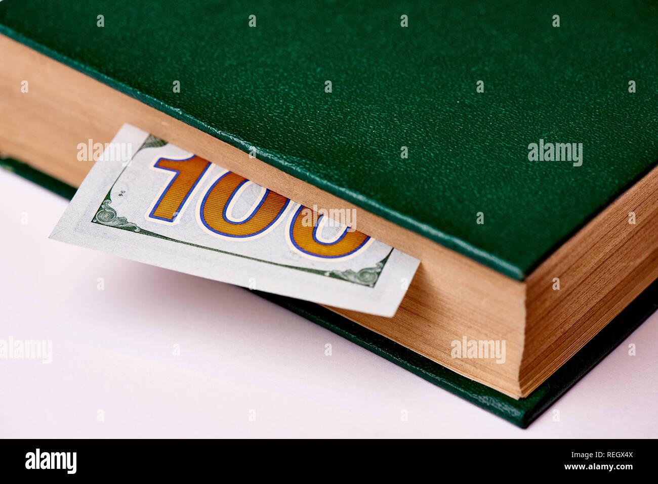 Bill vale cien dólares en libro sobre un fondo blanco macro. Foto de stock