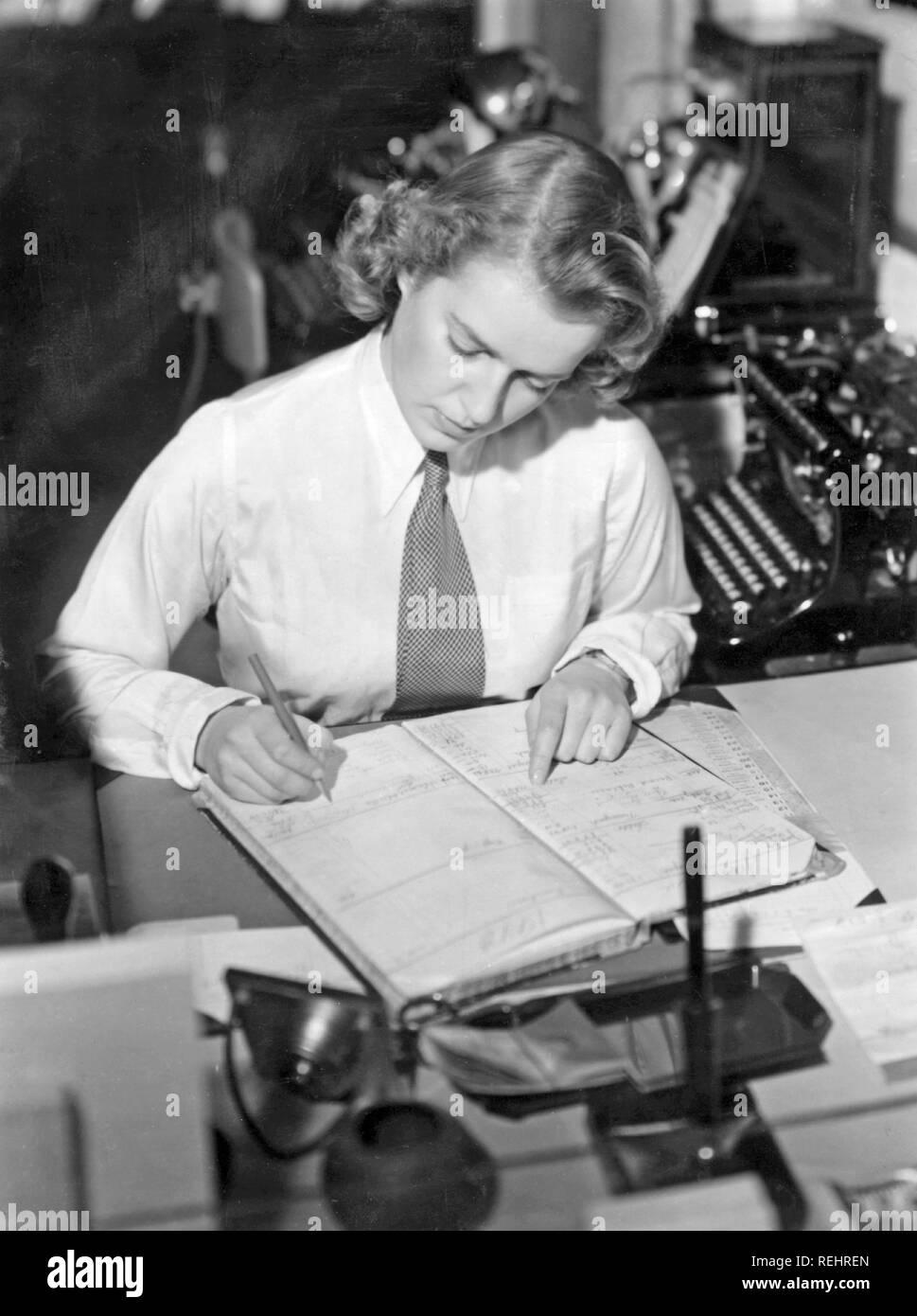 una blanca donde con tome cuidadosa y en joven registrer ella oficina corbata una clerk está Una Ella en 1940 camisa nota mujer Office vestido 18YqY