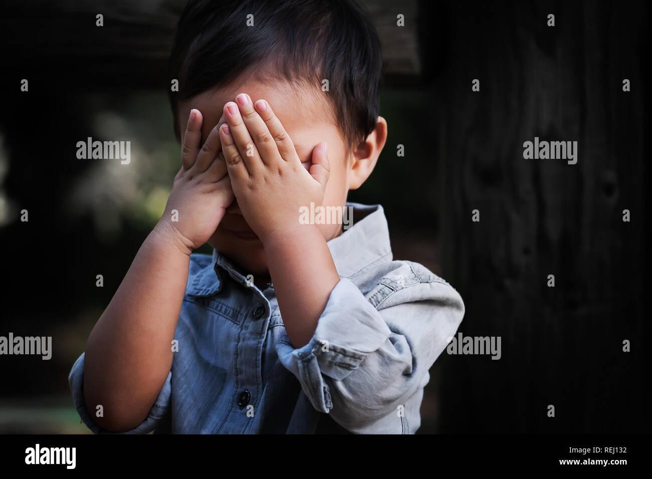 Un joven niño de edad que cubre su rostro con las manos, mostrando signos de ansiedad, miedo y decepción. Foto de stock