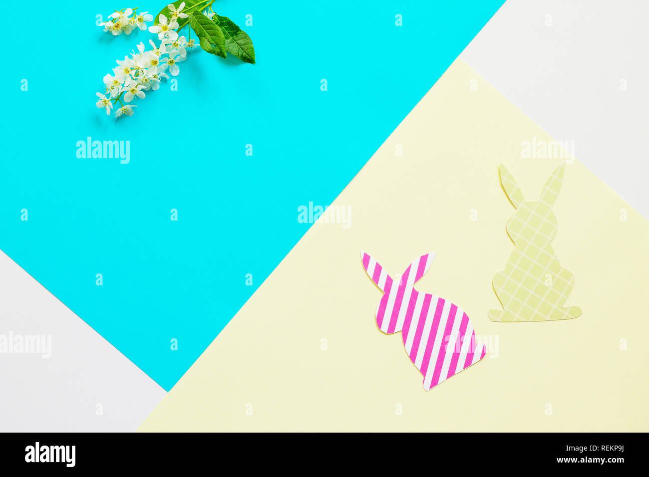 Conejito de Pascua de papel y las flores de la primavera. Mínimo concepto de pascua. Vista superior de la lay de fondo plano. Copie el espacio. Foto de stock