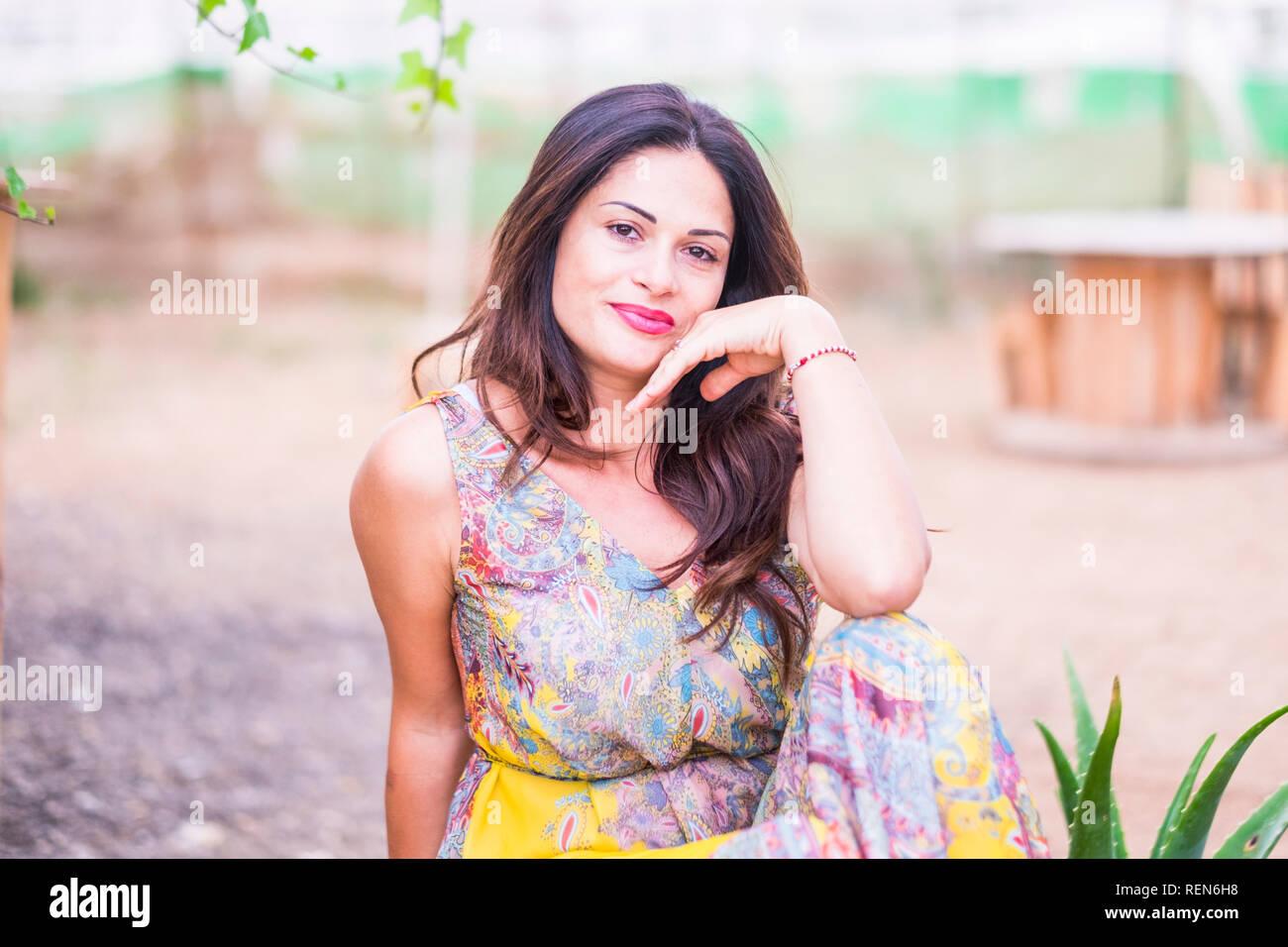5cff2bc58 Hermosa mujer joven posando con vestido de color sonriendo ante la cámara  exterior - gente agradable