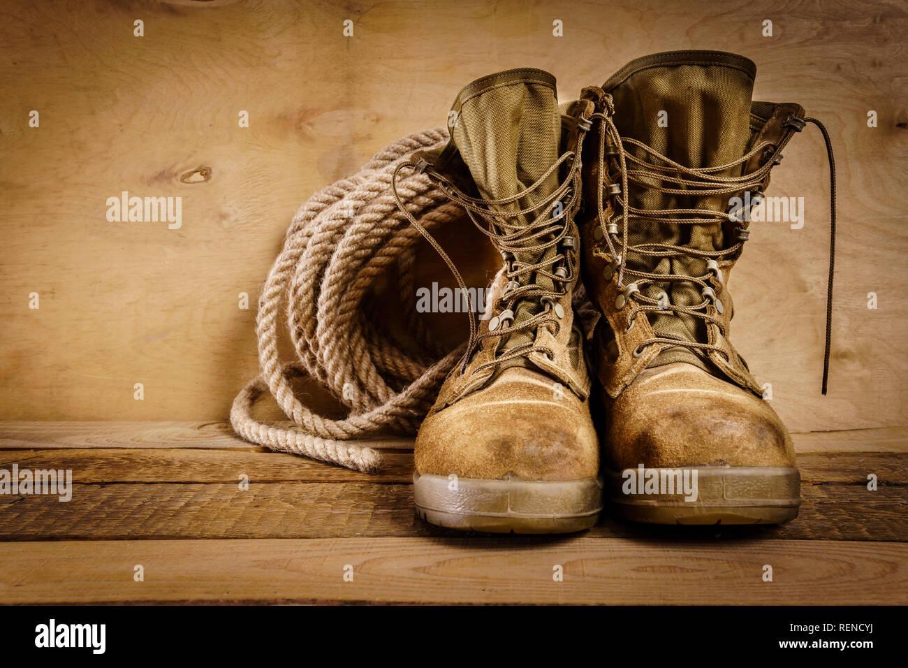 Viejas botas militares y cuerda sobre una mesa de madera Imagen De Stock