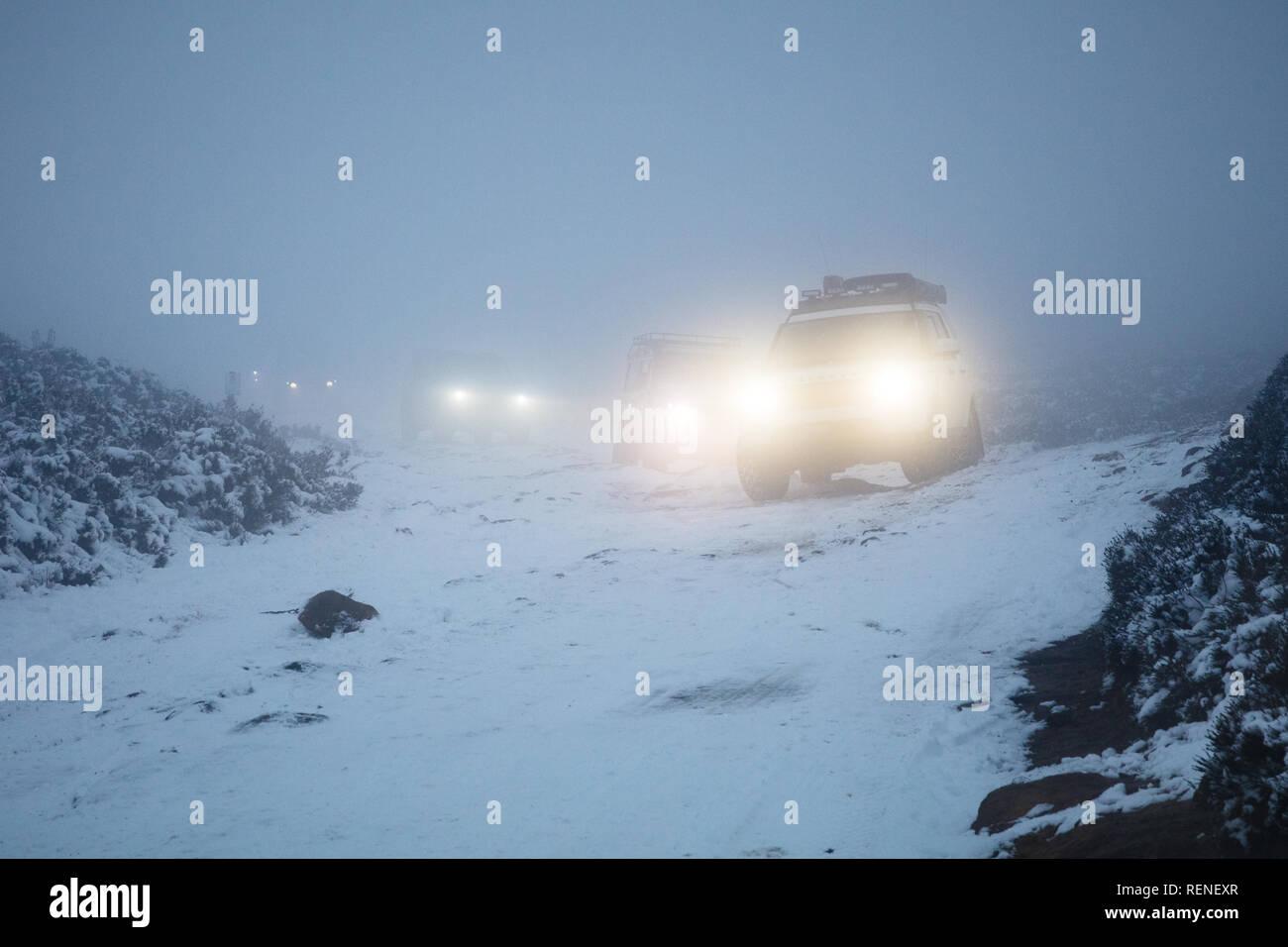 Un convoy de vehículos todoterreno navegar por una pista cubierta de nieve en la densa niebla. Houndkirk Road, Peak District National Park, Sheffield, South Yorkshire, Eng Foto de stock