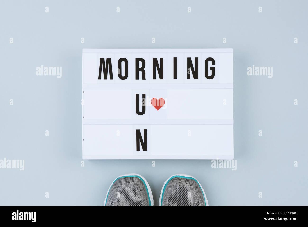 Texto de motivación en caja de luz mañana y zapatillas deportivas sobre  fondo gris fd5beae88ed29