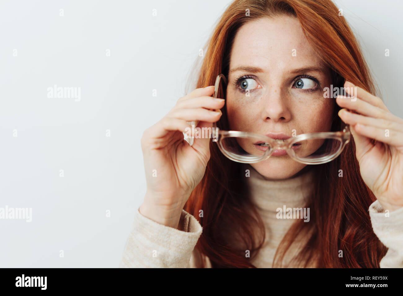 Mujer atractiva quitando sus gafas de vista de lado con ojos muy abiertos hacia la copia en blanco espacio en blanco Foto de stock