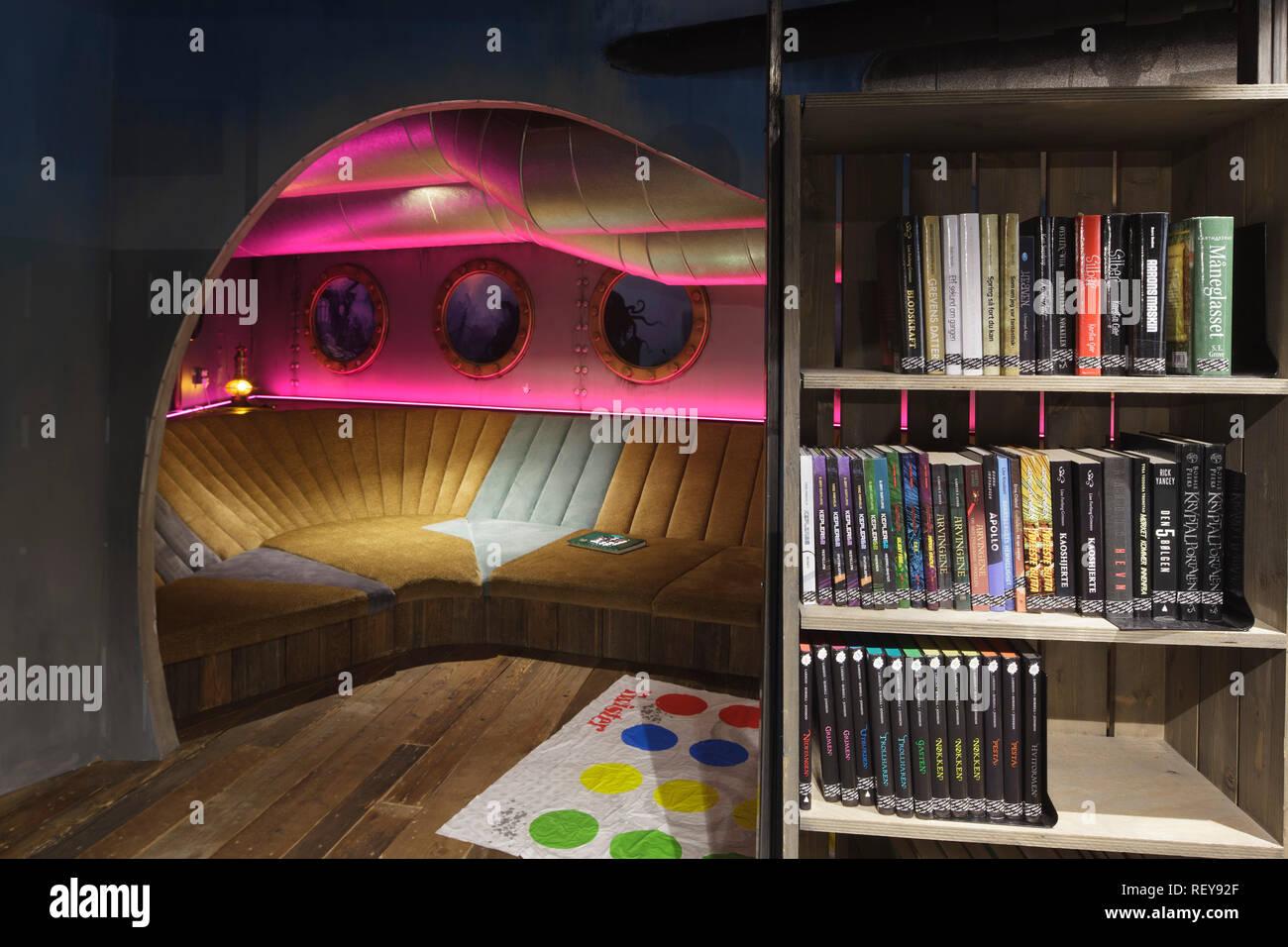 Submarino-themed asientos, con sobrecarga portillas y rosa iluminación y estantería a la derecha. Biblo Deichman Toyen biblioteca infantil, Oslo, Noruega Imagen De Stock