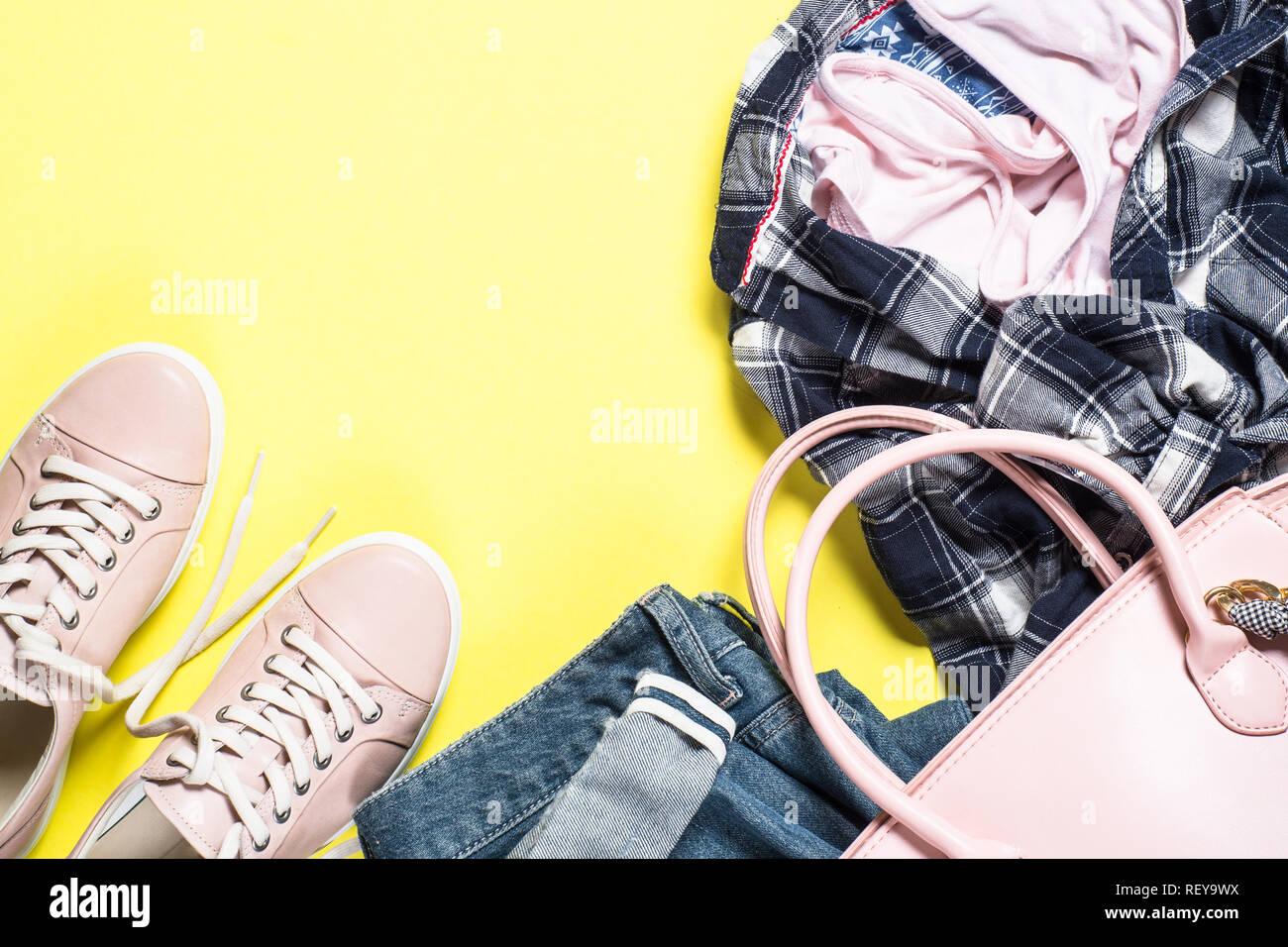 c8699472 Mujer moda set - zapatos de tela rosa, top y jeans sobre fondo amarillo.  Vista superior del espacio de copia.