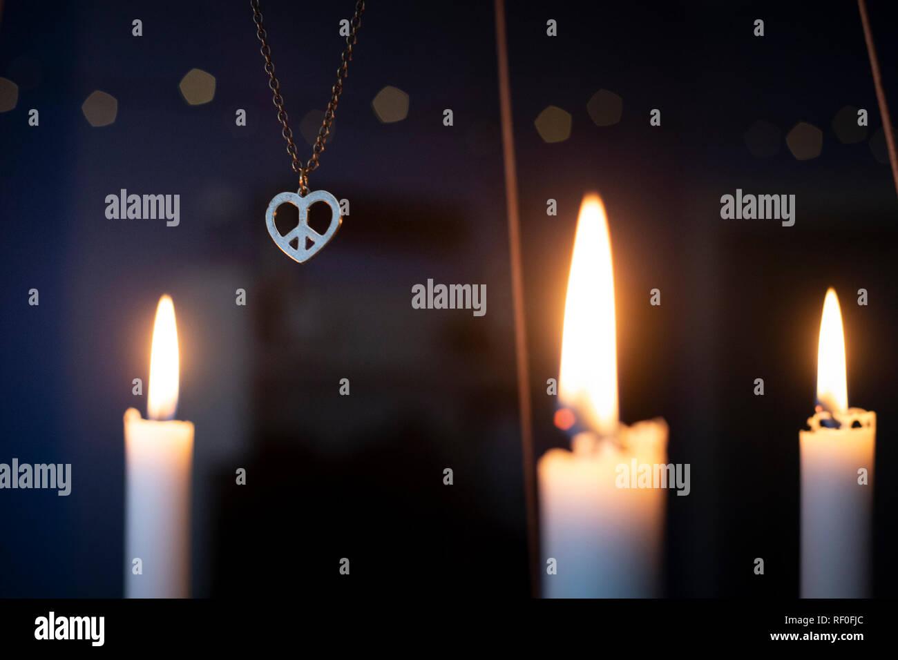 La paz, el amor, la navidad fondo con un símbolo del corazón de paz entre velas colgantes Colgante de oro resplandeciente candelabro de Adviento. Foto de stock