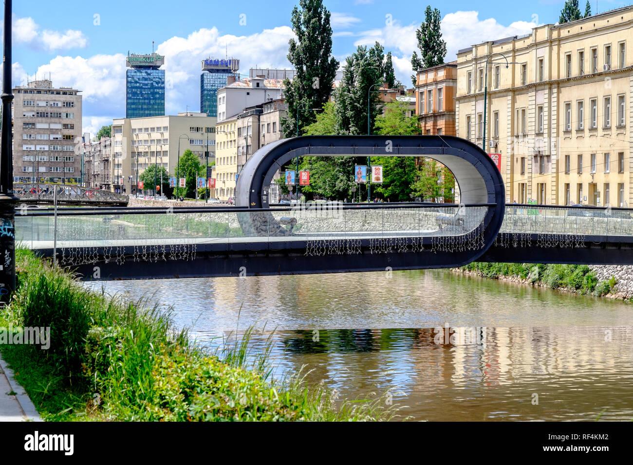 """Festina lente (en latín 'make prisa despacio"""") puente sobre el río Miljacka en Sarajevo - el diseño del bucle funky exhorta a los peatones a disfrutar de la vista Imagen De Stock"""
