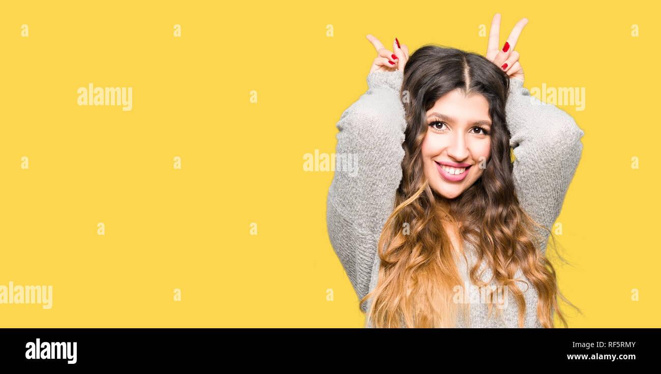 Hermosa joven mujer vistiendo vestidos invierno posando gracioso y loco con los dedos en la cabeza como orejas de conejo, sonriendo alegre Foto de stock
