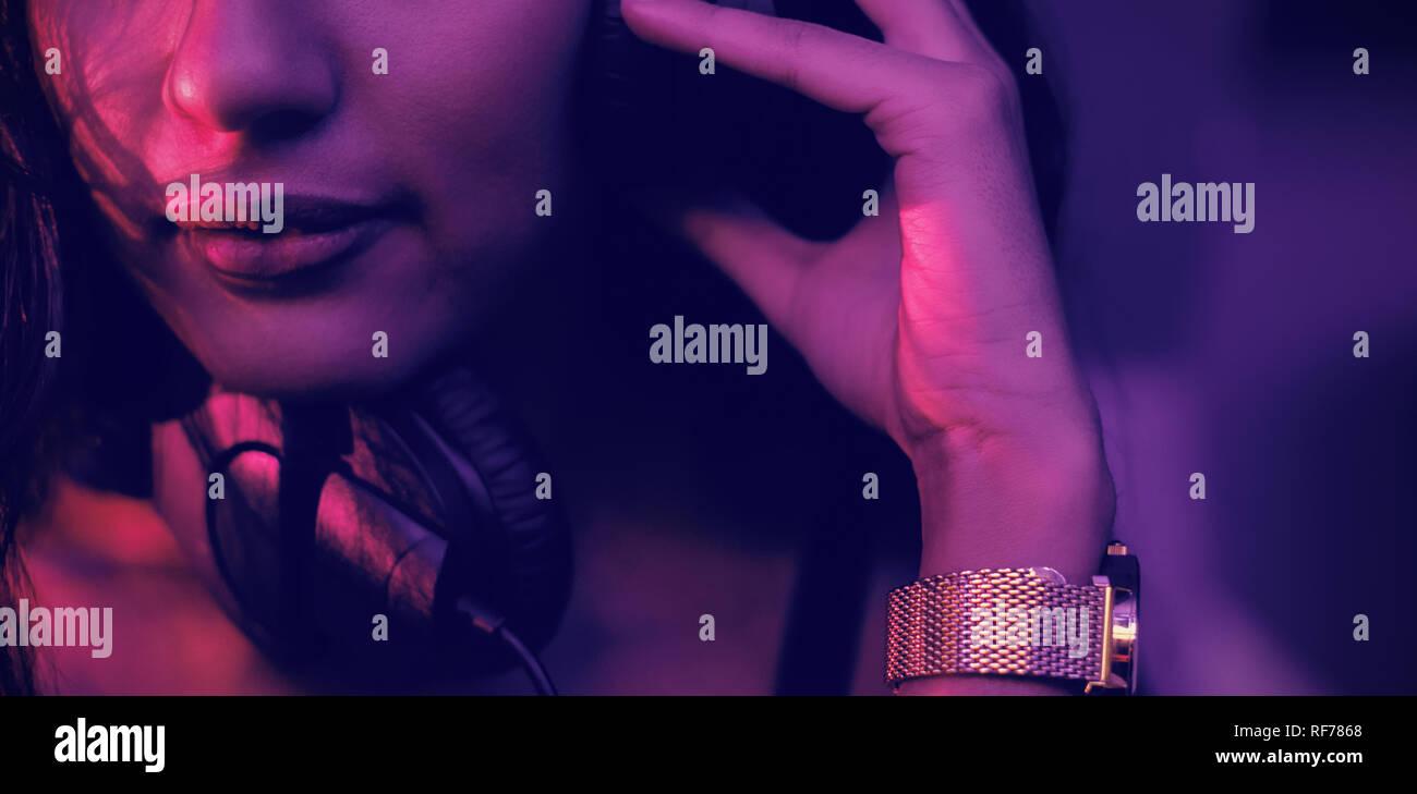 Dj femenina escuchando música en auriculares Foto de stock