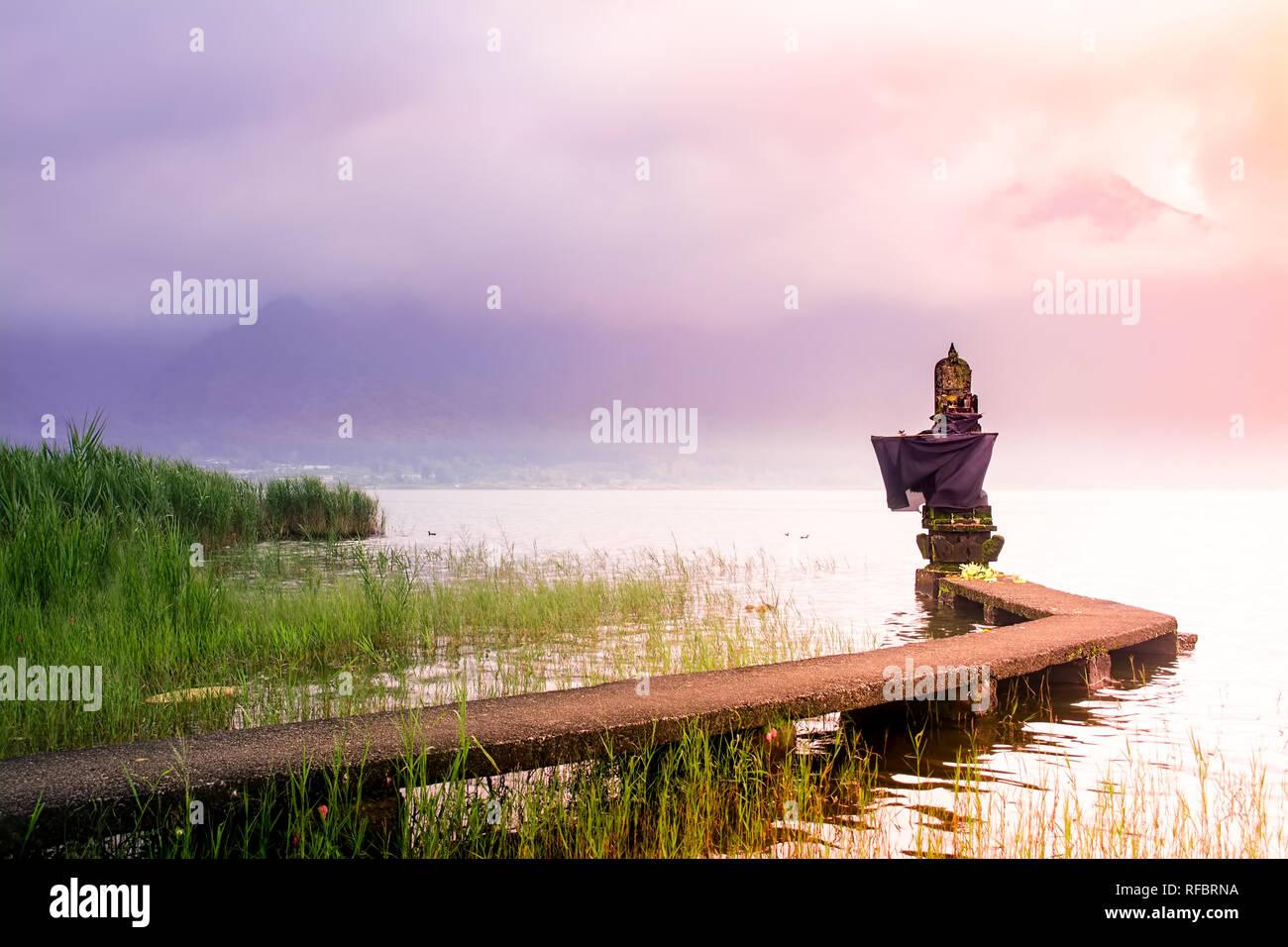 Pequeño templo hindú en el Lago con el puente de conexión durante el amanecer en Bali el día nublado y brumoso con la montaña como telón de fondo. Foto de stock