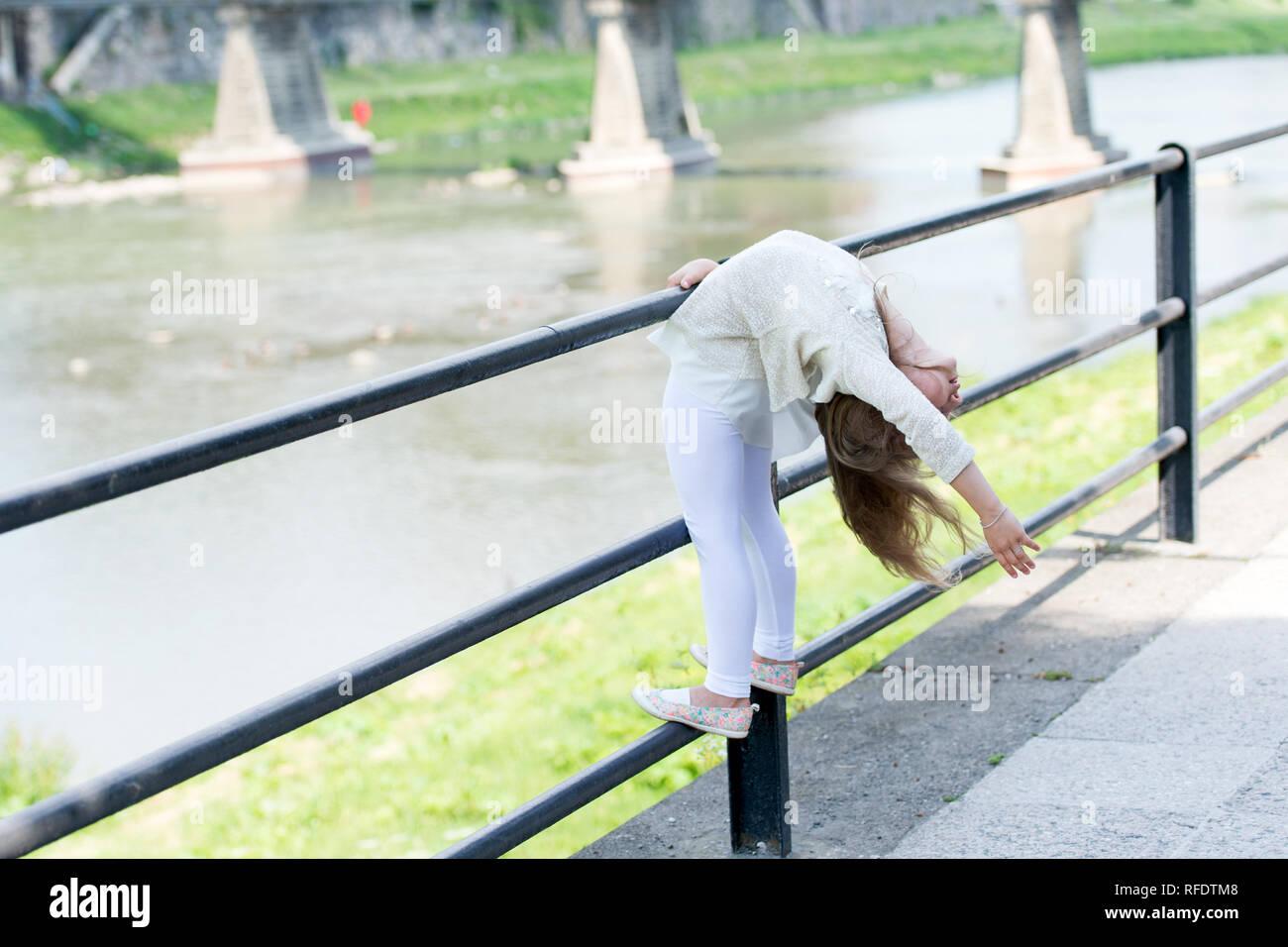 Chico Chica se flexiona hacia atrás como gimnasta flexible cerca de baranda en el Riverside de fondo. Chico Chica gimnasta demuestra la flexibilidad del cuerpo. Concepto de flexibilidad. Niño Niña deportivo flexible gimnasta. Imagen De Stock