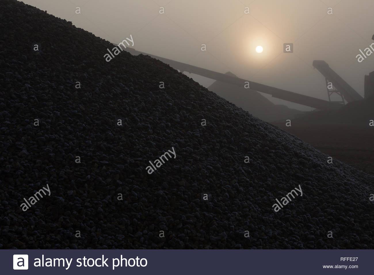 Montones de agregado en la niebla son silhoutted contra el sol de primera hora de la mañana Imagen De Stock