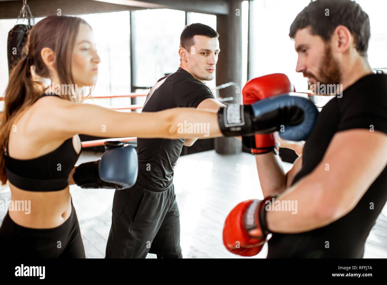 El hombre y la mujer capacitación para caja con entrenador personal en el cuadrilátero de boxeo en el gimnasio Foto de stock