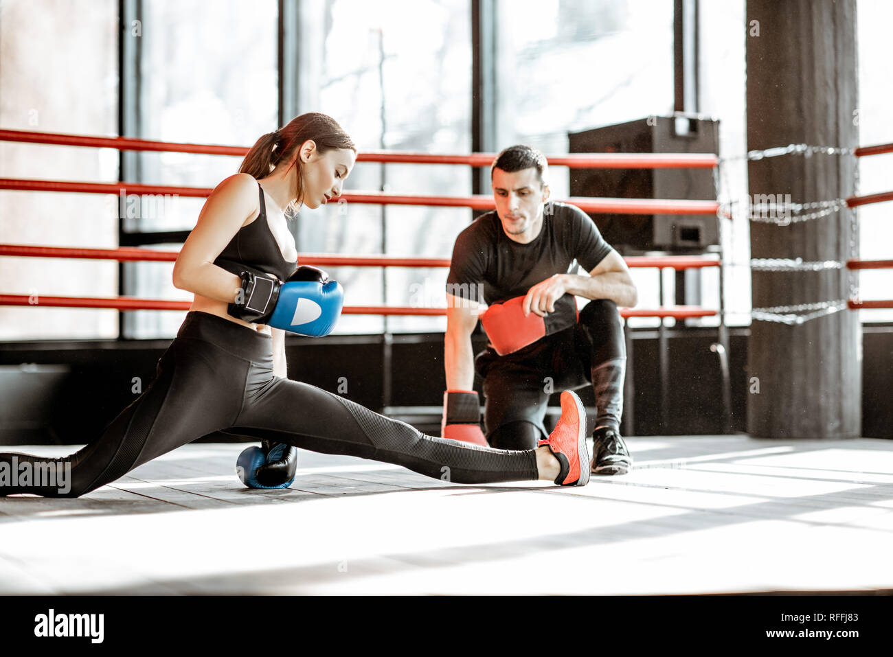 Mujer joven formación a caja con entrenador personal en el cuadrilátero de boxeo en el gimnasio Foto de stock