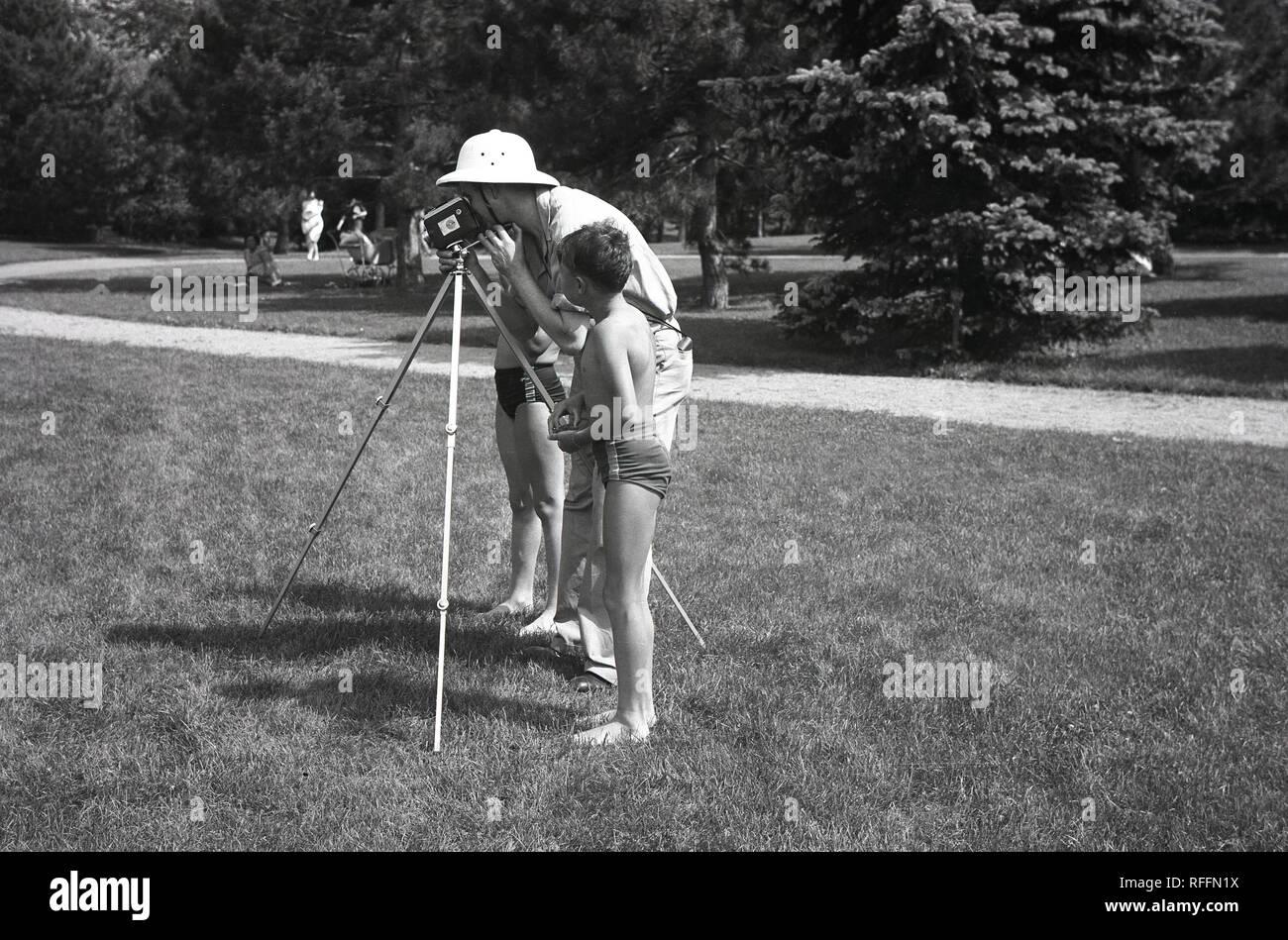1950s, históricos, dos chicos jóvenes en trajes de pie por un hombre con un trípode grabando con una película en casa o cine-cámara en un parque. En esta época. o para grabar los momentos en familia con una pequeña cámara de cine portátil era un pasatiempo muy popular y hay muchos formatos diferentes y cámaras disponibles. Imagen De Stock