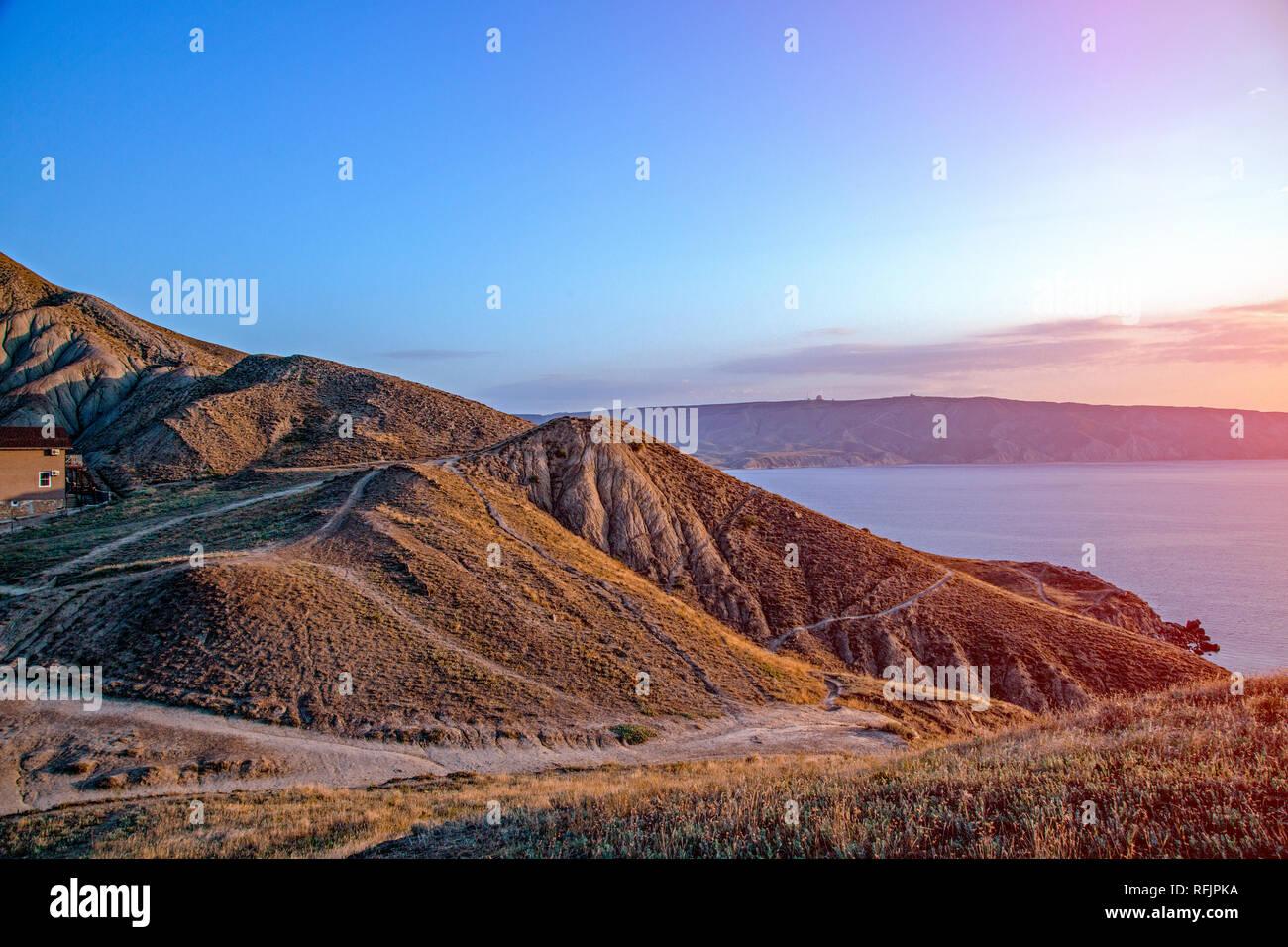 Impresionantes vistas al mar desde la cima de la colina con la puesta de sol Foto de stock