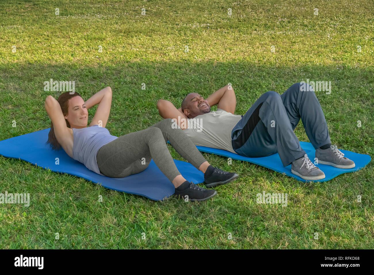 Empiezan haciendo situps sobre colchonetas para yoga en el césped como parte de la rutina de ejercicios. Una vida saludable es importante para una pareja moderna. Imagen De Stock