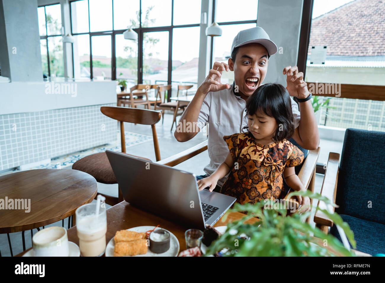 Niño molestar a su papá mientras trabaja Foto de stock