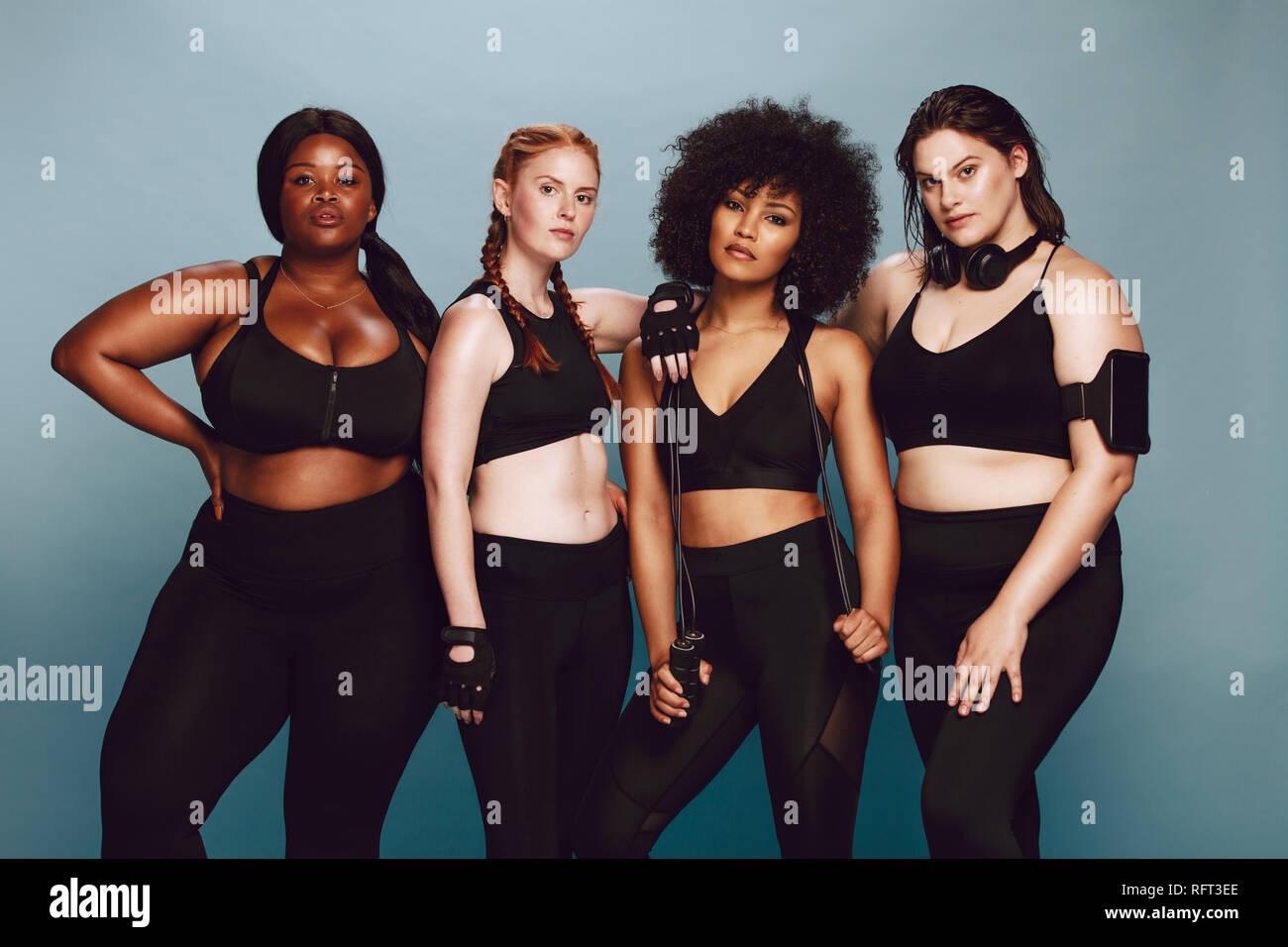 Grupo de mujeres de diferentes razas y el tamaño del cuerpo vestido con ropa deportiva juntos contra un fondo gris. Diversas mujeres en ropa deportiva looki Imagen De Stock