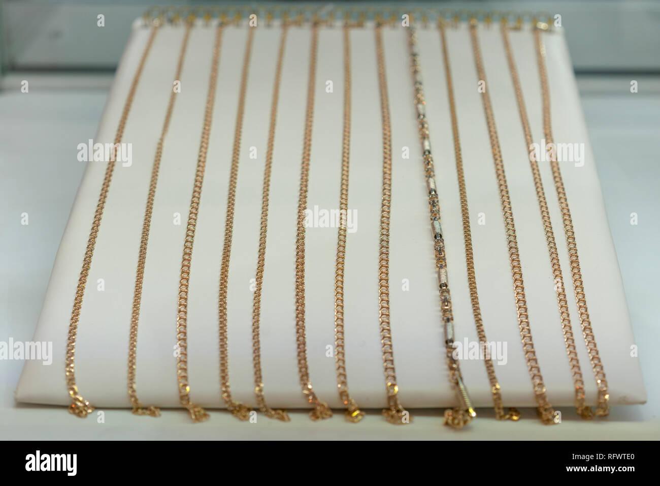 5b44e1aec772 Cadenas de oro en la vitrina de la joyería de oro. Collar de oro en fondo  rojo en el escaparate de lujo joyas - joyería de oro brillante cadena de  platino