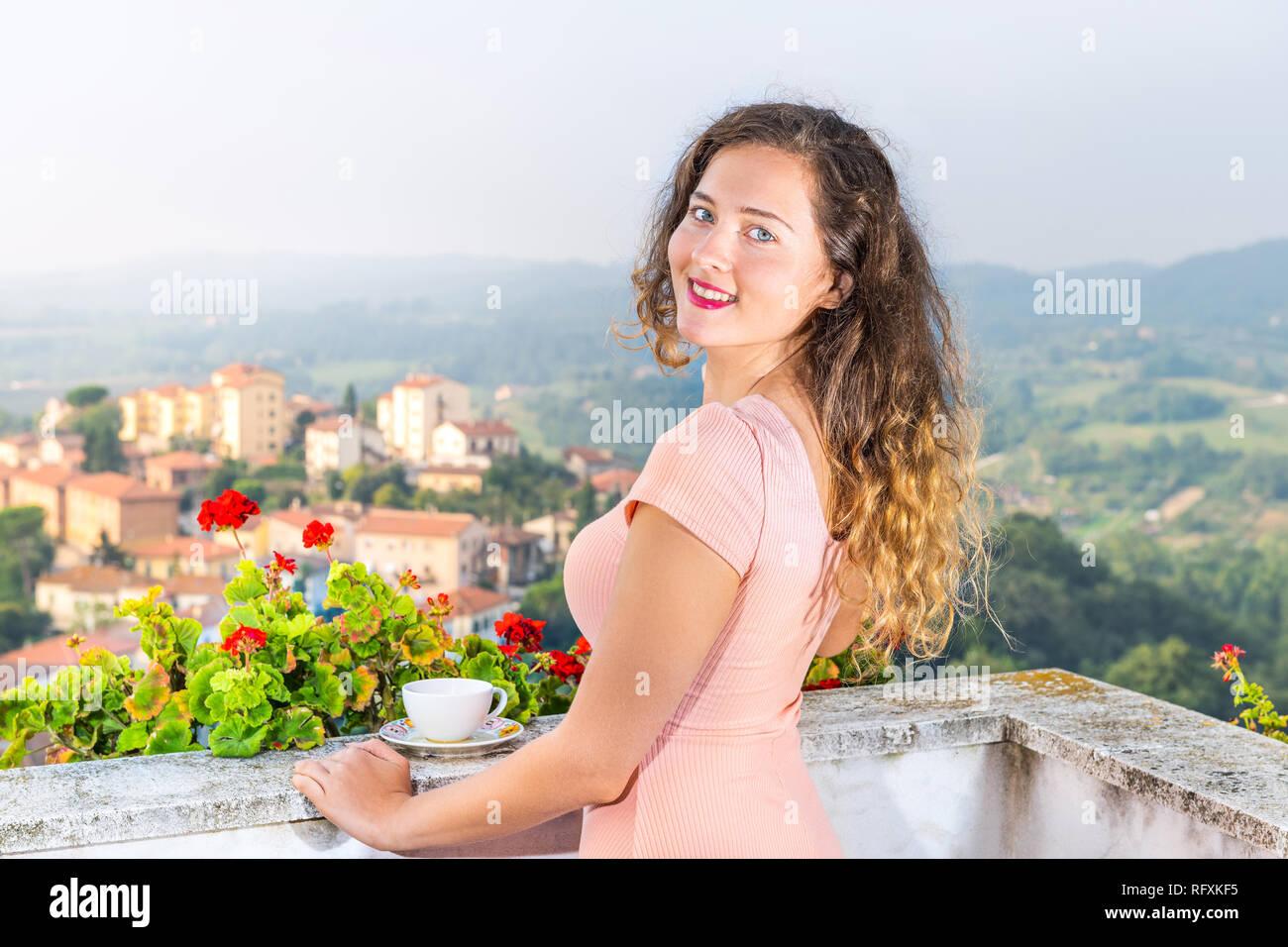 Taza de té café en el balcón terraza de geranio rojo flores fuera de Italia con vistas al paisaje urbano de Chiusi colinas de Toscana y Umbría cerca youn Foto de stock