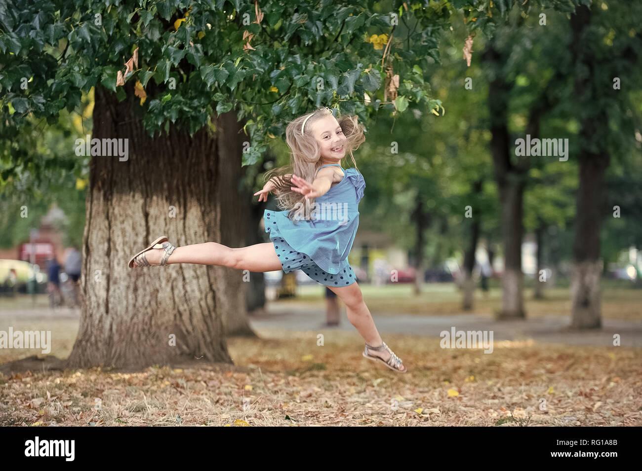 8bc21cd7a6b Niña bailarina saltar en verano park. Danza infantil en vestido azul ...
