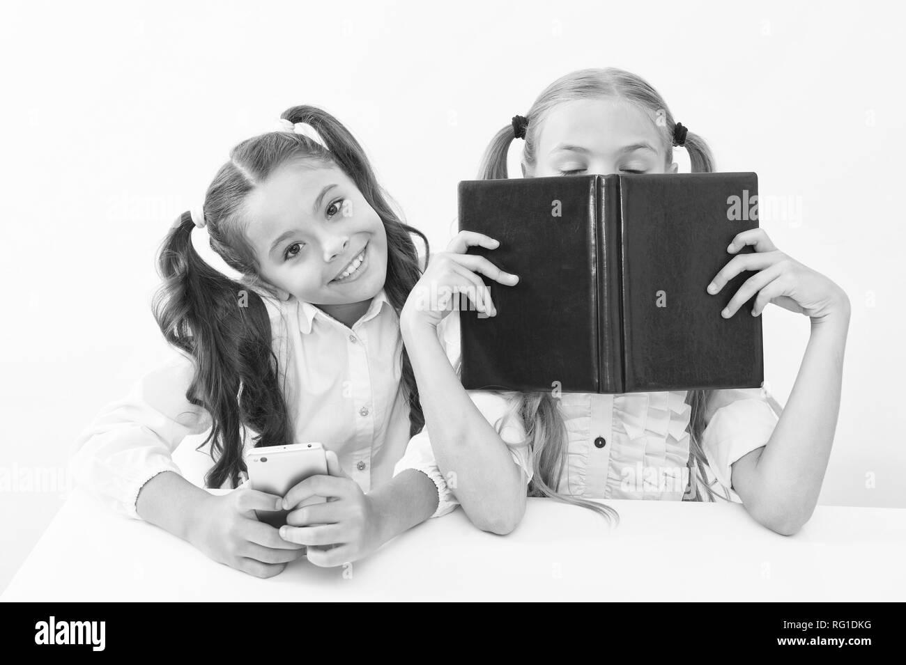 Contra la vieja escuela moderna. Colegiala mantenga teléfono móvil smartphone moderno mientras su amiga disfrute de libro viejo como almacenamiento de datos analógicos. Tecnología contra la experiencia. Nueva generación de demandas educativas. Foto de stock
