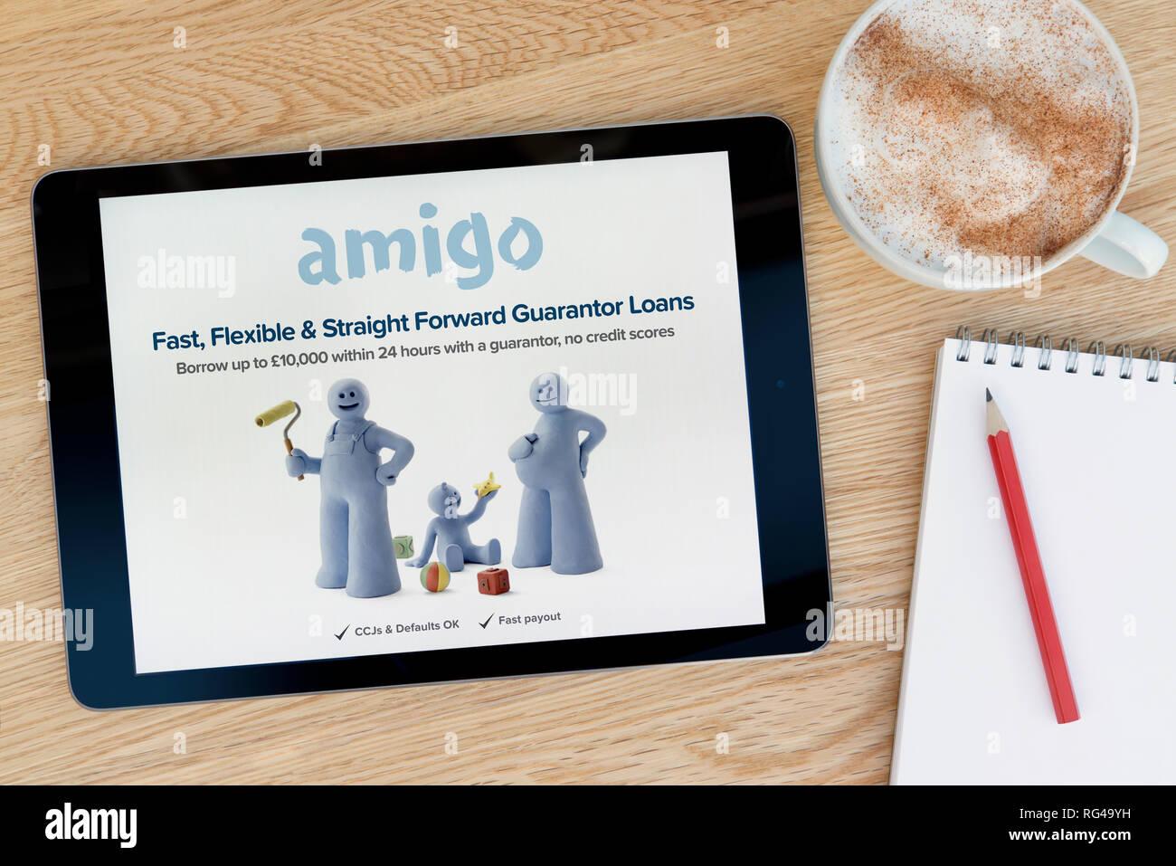 La Amigo préstamos características del sitio web en un dispositivo tablet iPad que descansa sobre una mesa de madera junto a un bloc de notas (sólo para uso editorial). Imagen De Stock