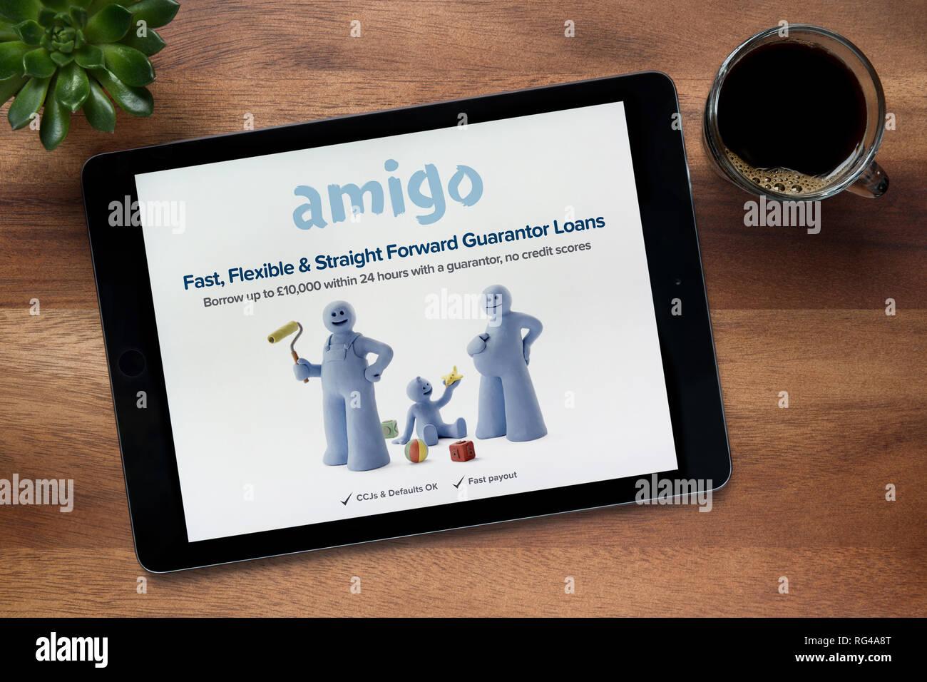 El sitio web de Amigo préstamos es visto en un iPad, en una mesa de madera junto con un café espresso y una planta de casa (Editorial). Imagen De Stock