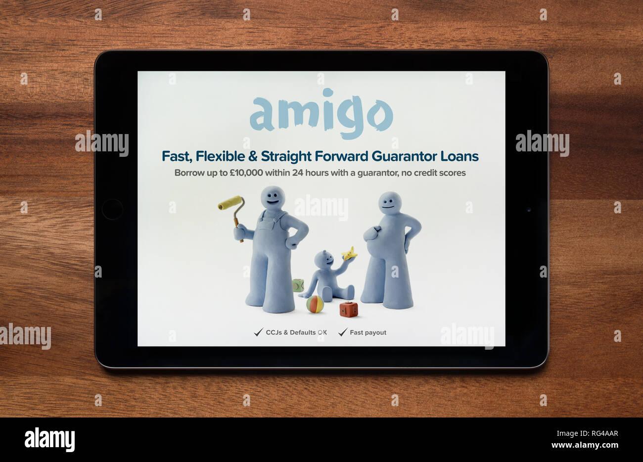 El sitio web de Amigo préstamos es visto en un iPad, que descansa sobre una mesa de madera (uso Editorial solamente). Imagen De Stock