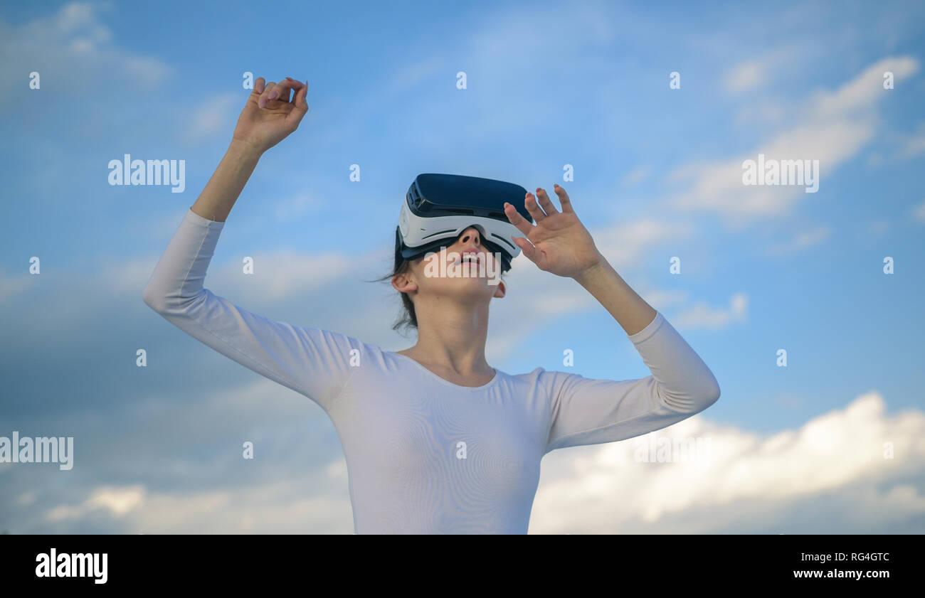 Parece tan real. Cute girl play en un entorno simulado. Mujer joven gesticulando en vr gafas. Pretty girl llevar casco de realidad virtual. Innovadora Imagen De Stock