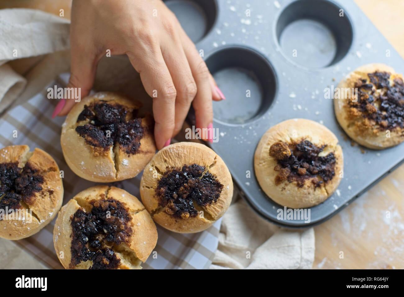 Mujer sacando muffins de la bandeja para hornear. Imagen De Stock