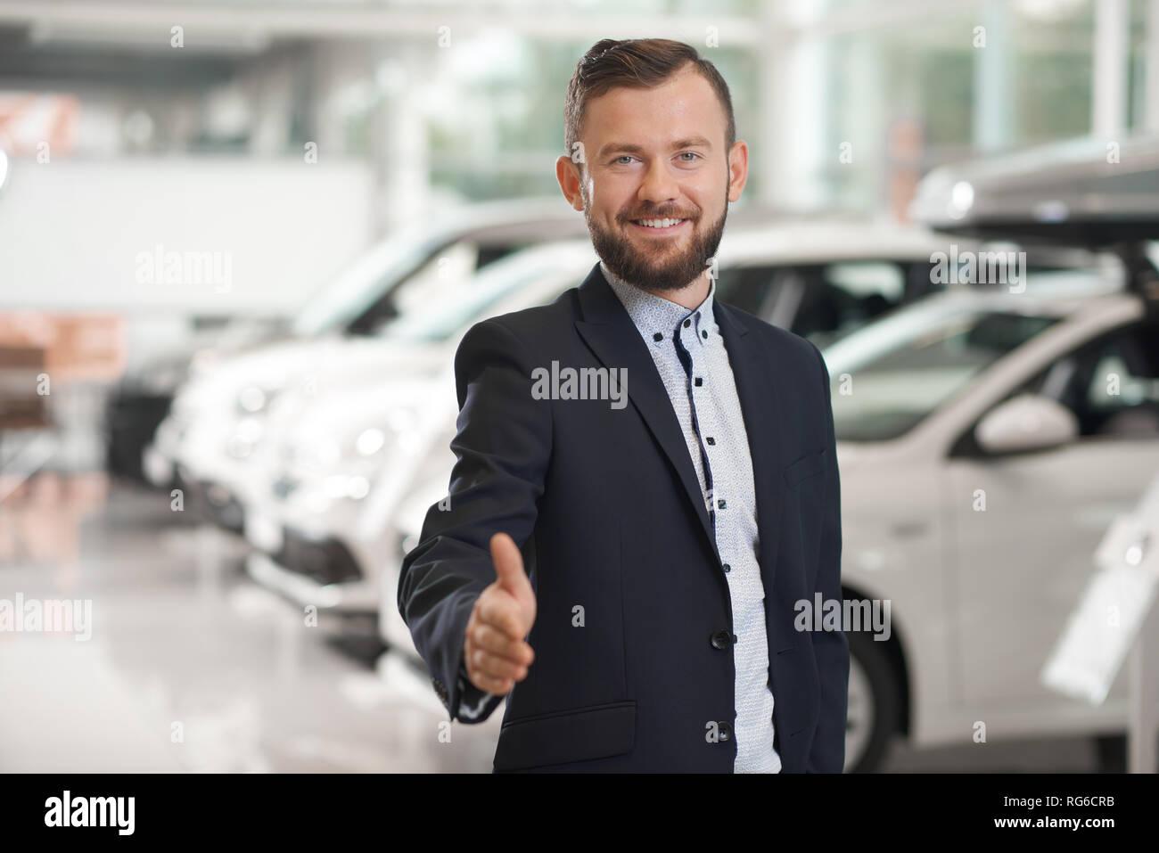 Apuesto gerente del concesionario de coches mirando a la cámara, sonriendo, posando. Concesionario de coches vistiendo la camiseta oficial, traje azul oscuro. Feliz hombre barbado mostrando el pulgar hacia arriba. Imagen De Stock
