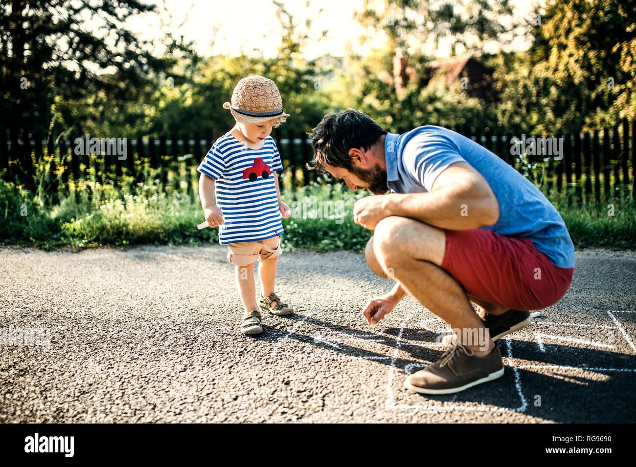 Padre Rayuela dibujo sobre el asfalto mientras su hijo pequeño mirándolo Foto de stock
