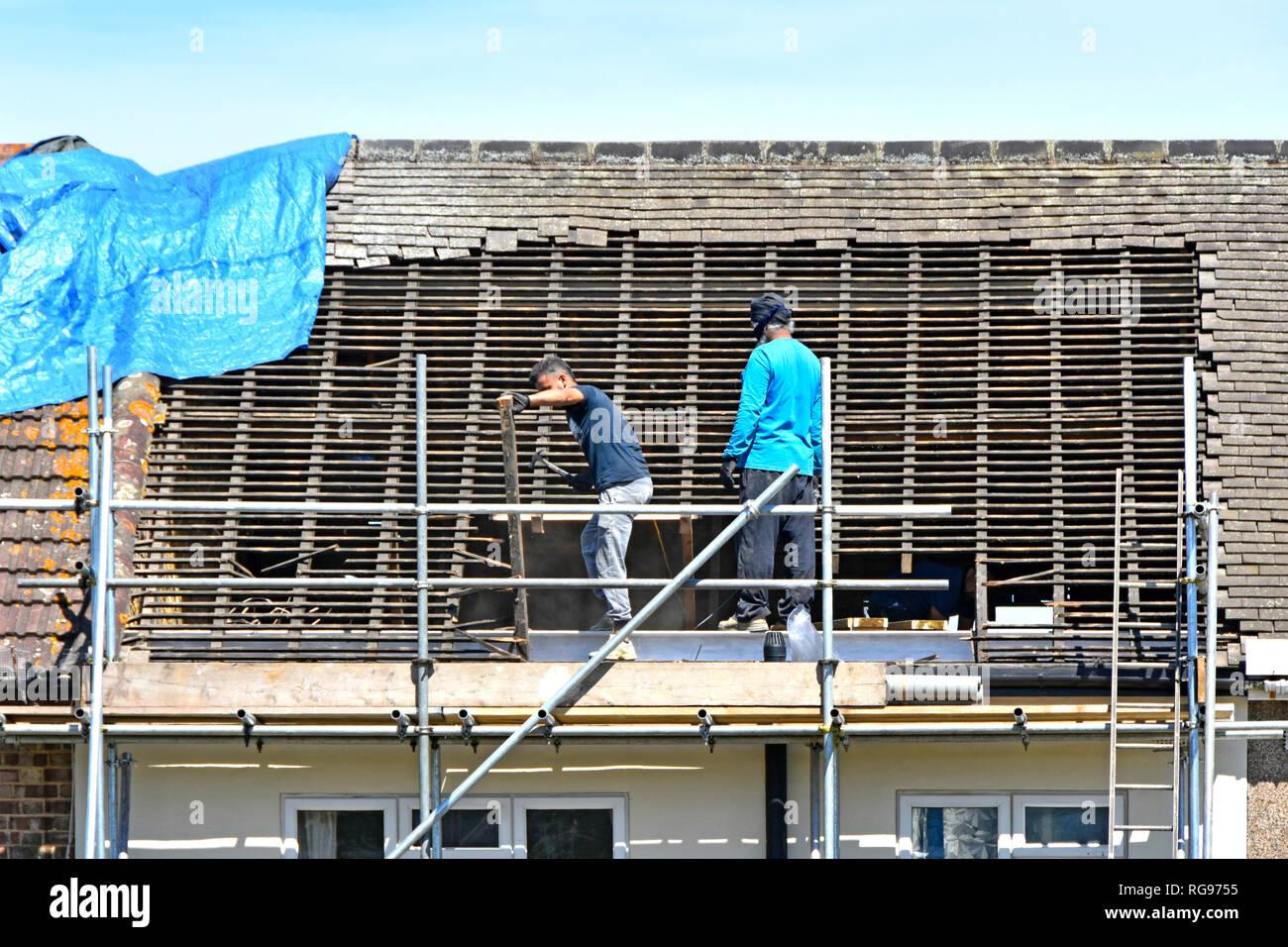 Los trabajadores en los andamios generador de extracción de madera y azulejos de techo en preparación para nuevos dormer habitación ático en el desván de la casa adosada Romford East London UK Imagen De Stock