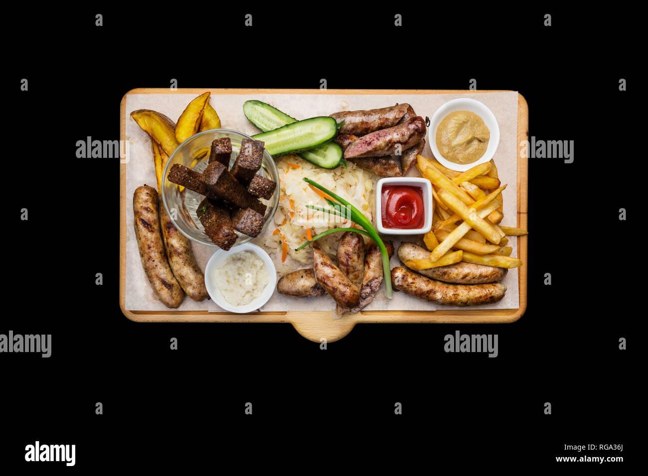 Bocadillos de cerveza. Salchichas asadas y papas fritas con tomate y salsa de barbacoa, servido en la tabla de cortar. Foto de stock