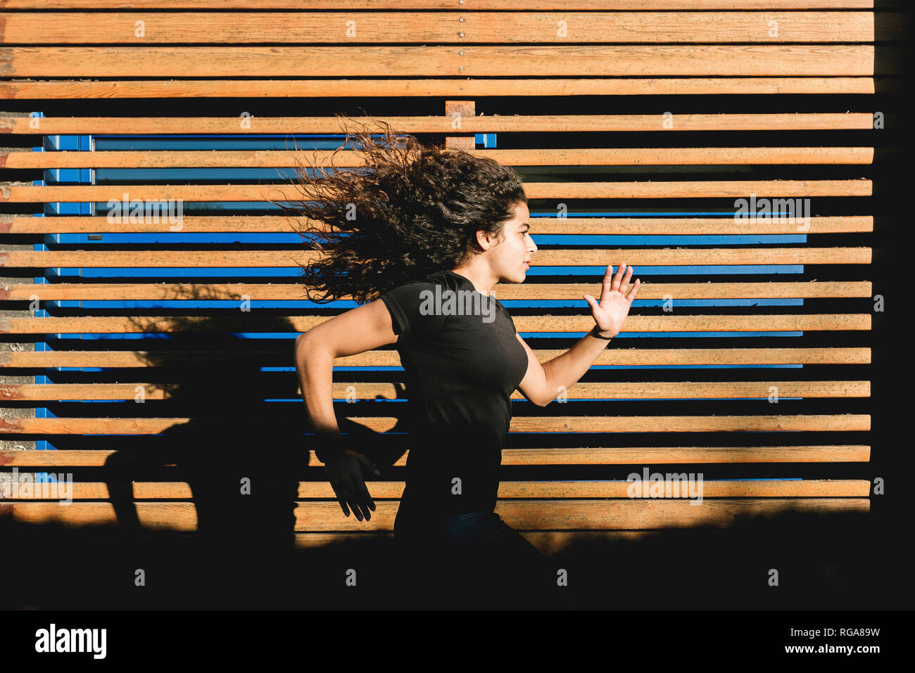 Sportive joven que corre a lo largo de paneles de madera Imagen De Stock