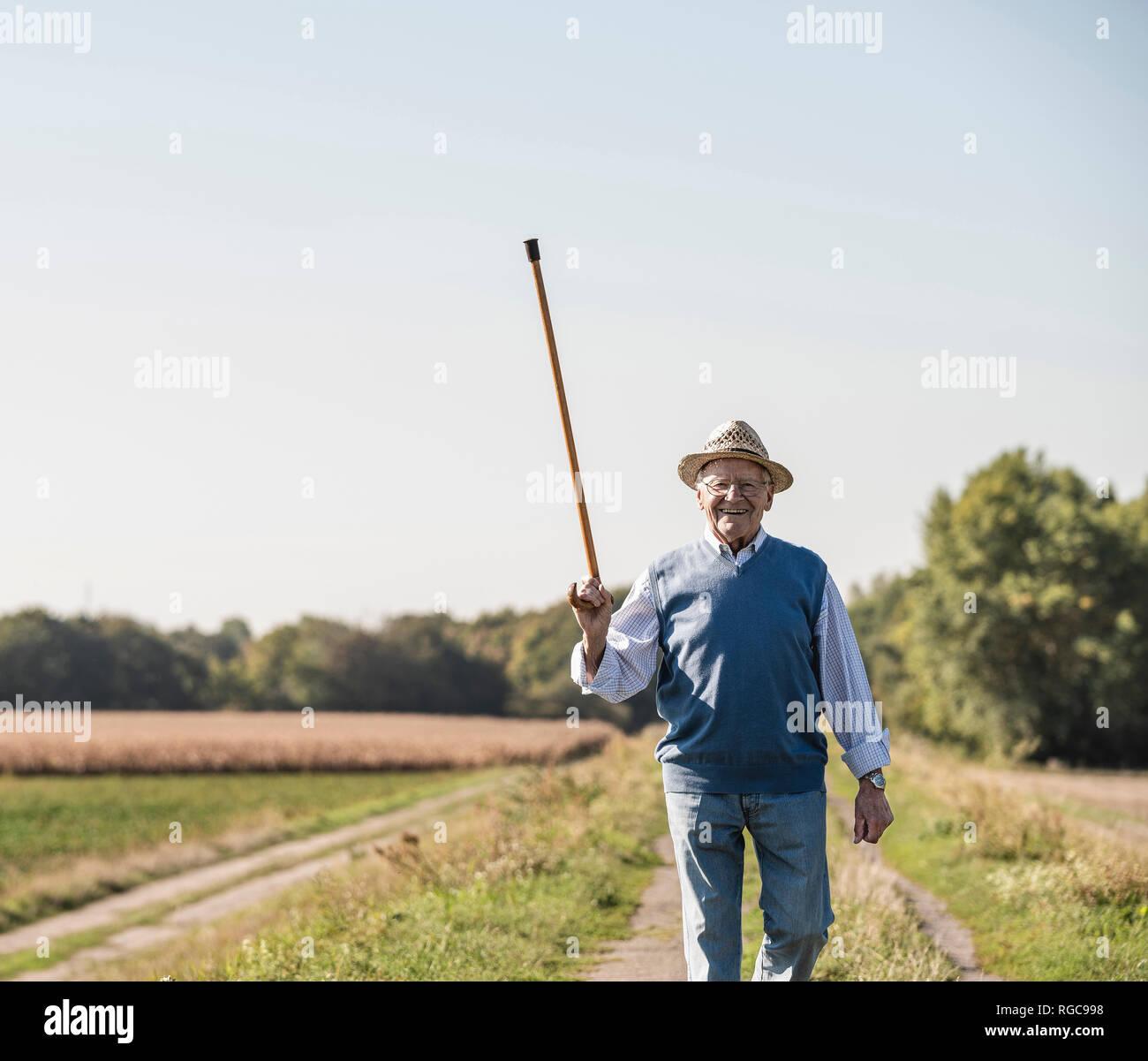 Altos hombre caminando en los campos, saludo con su bastón Foto de stock
