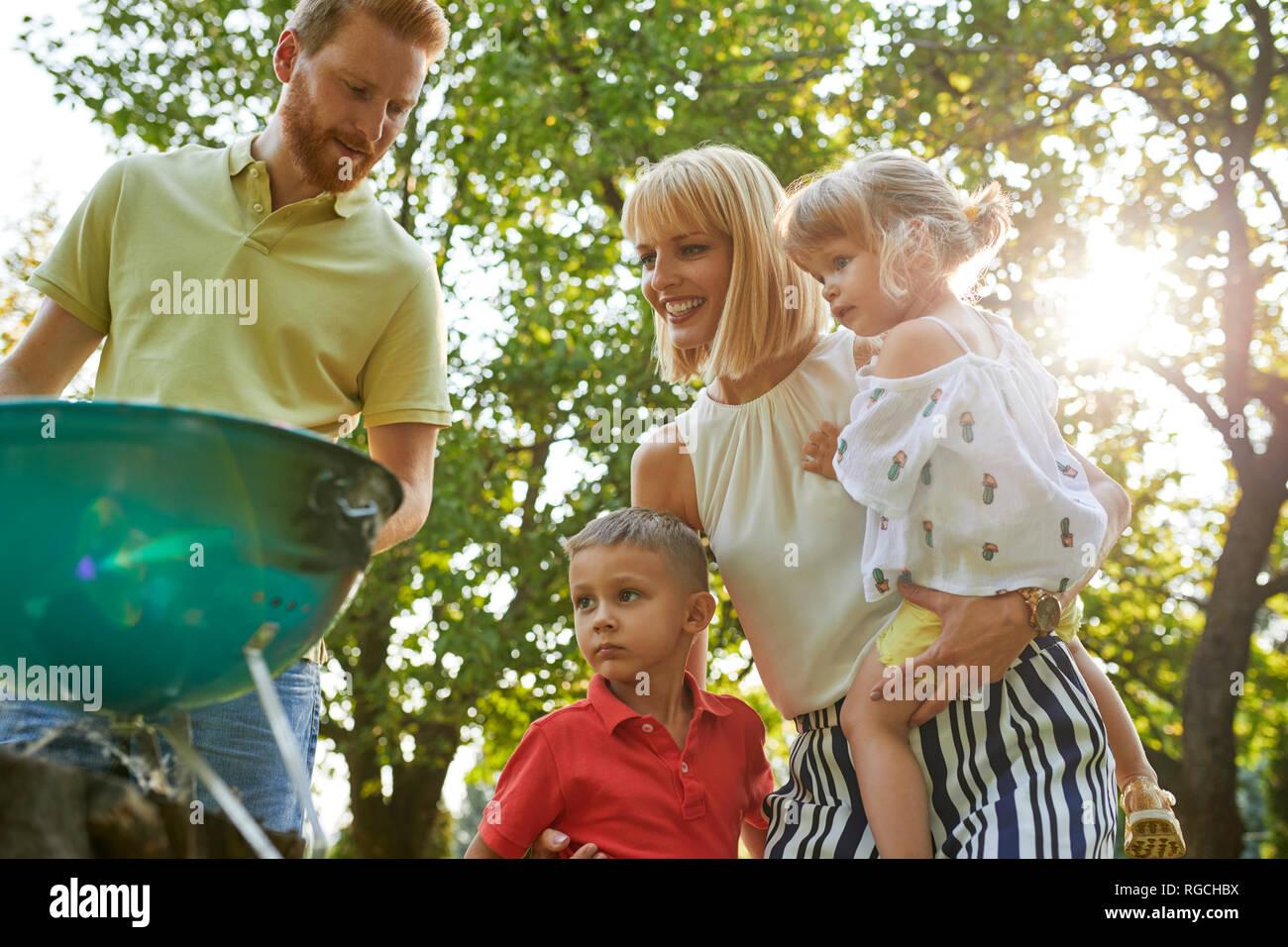 Familia tener una barbacoa en el jardín Foto de stock